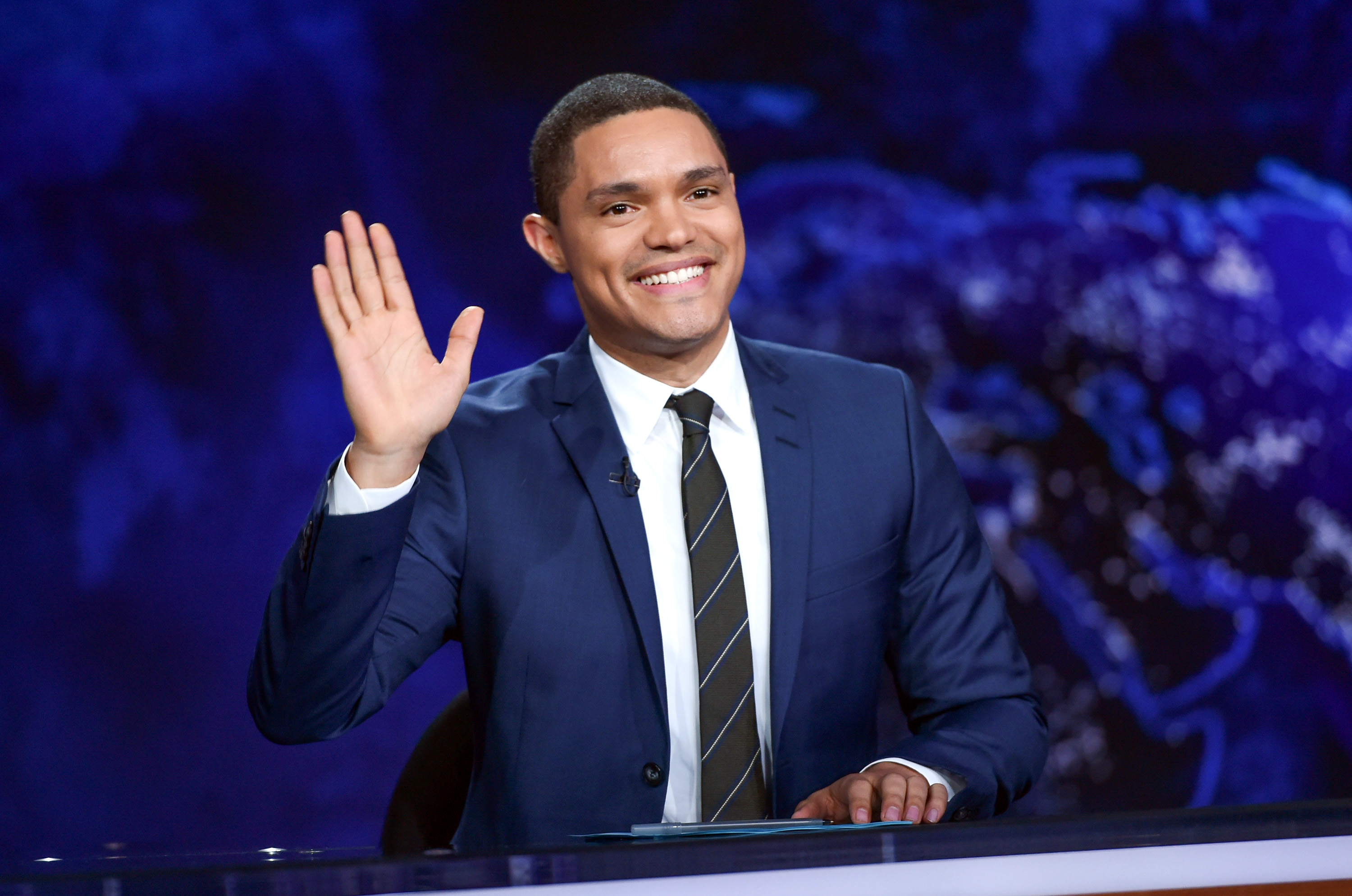 "FILe - In this Sept. 29, 2015 file photo, Trevor Noah gestures on the set during a taping of ""The Daily Show with Trevor Noah"" in New York. One day after an emergency appendectomy, Trevor Noah was expected back at his ""Daily Show"" anchor desk, taping a new episode set to air Thursday night.  (Photo by Evan Agostini/Invision/AP, File)"