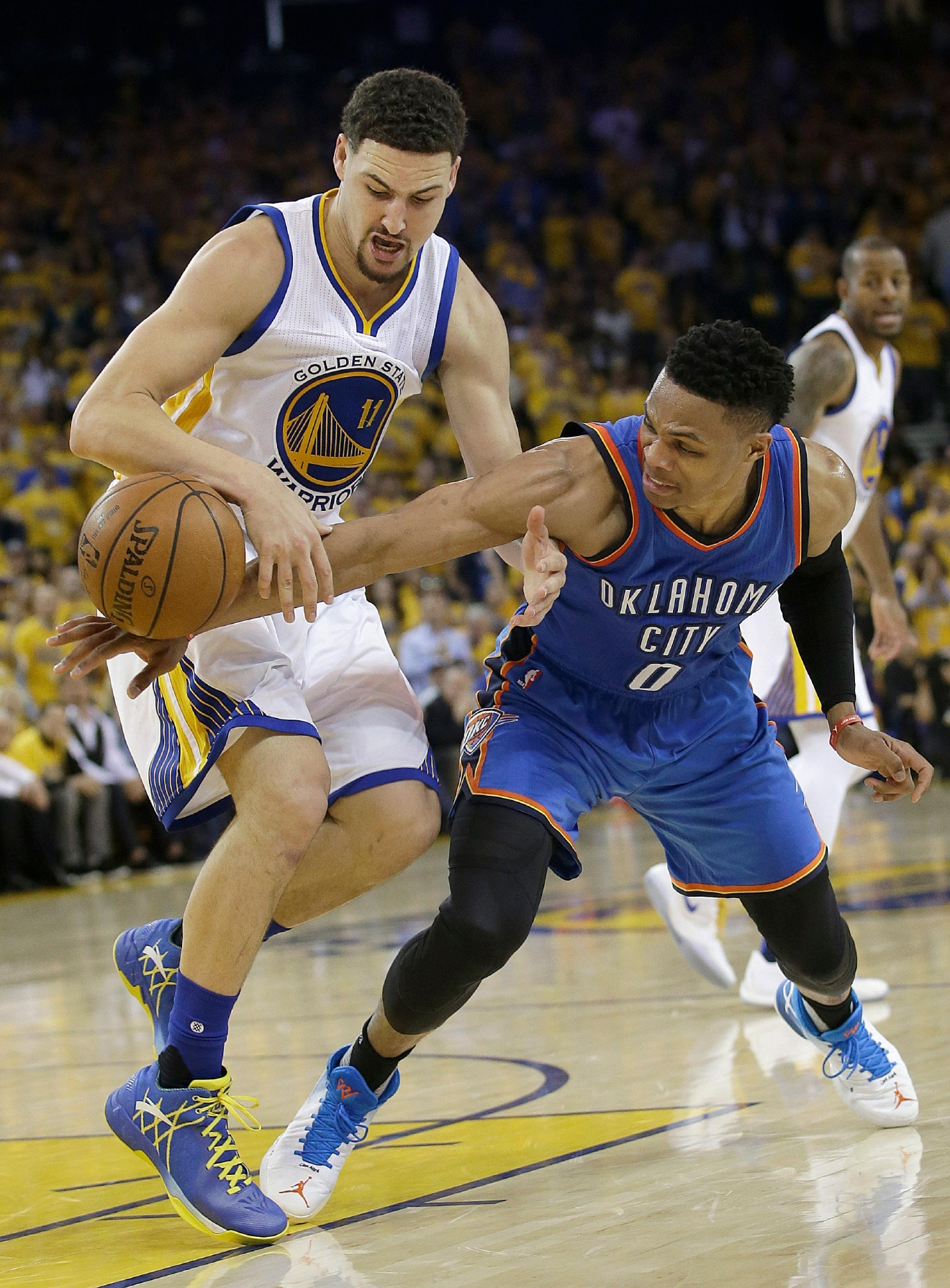Oklahoma City Thunder guard Russell Westbrook (0) reaches for the ball under Golden State Warriors guard Klay Thompson (11) during the first half of Game 5 of the NBA basketball Western Conference finals in Oakland, Calif., Thursday, May 26, 2016. (AP Photo/Marcio Jose Sanchez)