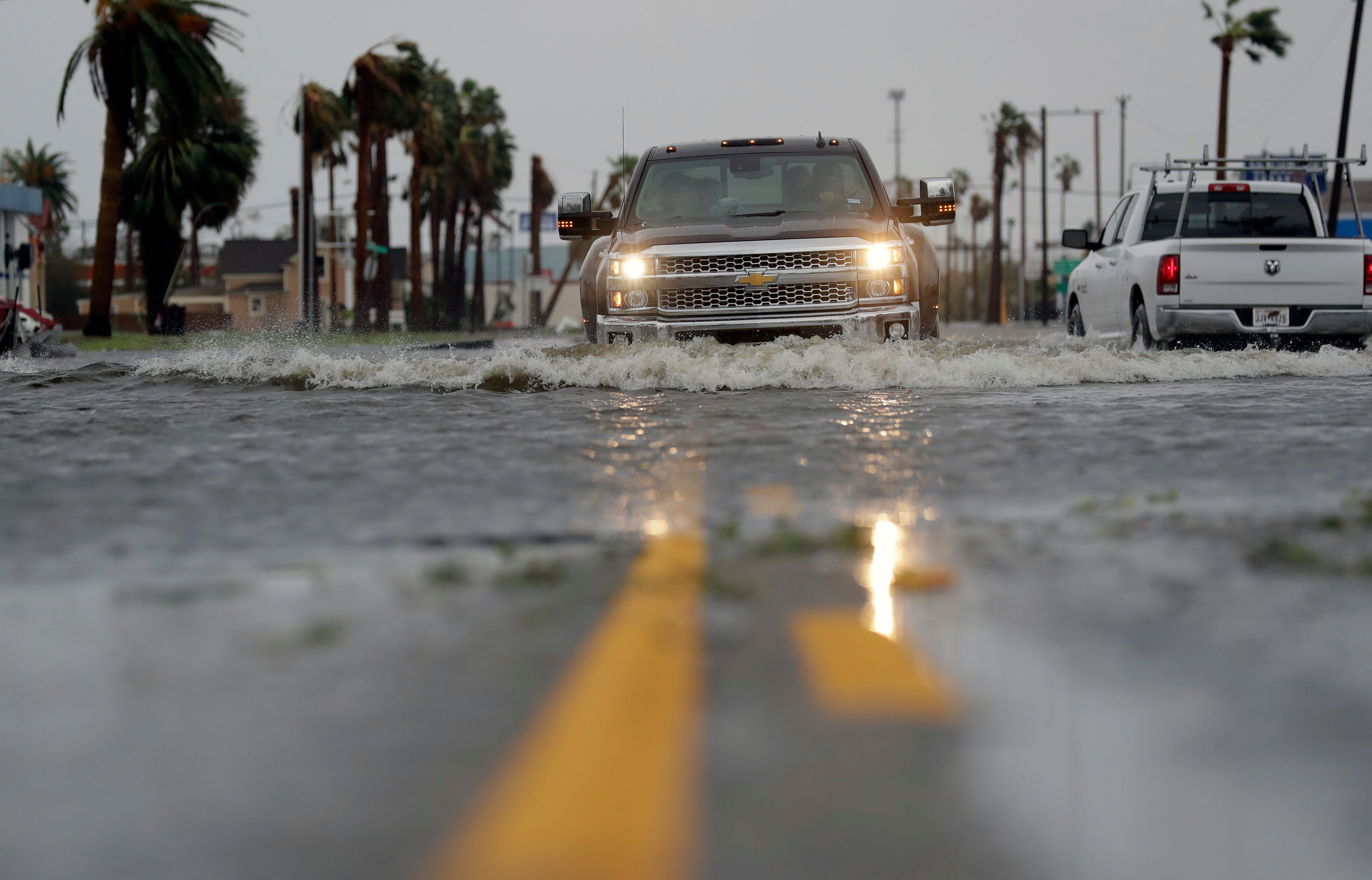 A drives moves through flood waters left behind by Hurricane Harvey, Saturday, Aug. 26, 2017, in Aransas Pass, Texas.   Harvey rolled over the Texas Gulf Coast on Saturday, smashing homes and businesses and lashing the shore with wind and rain so intense that drivers were forced off the road because they could not see in front of them. (AP Photo/Eric Gay)