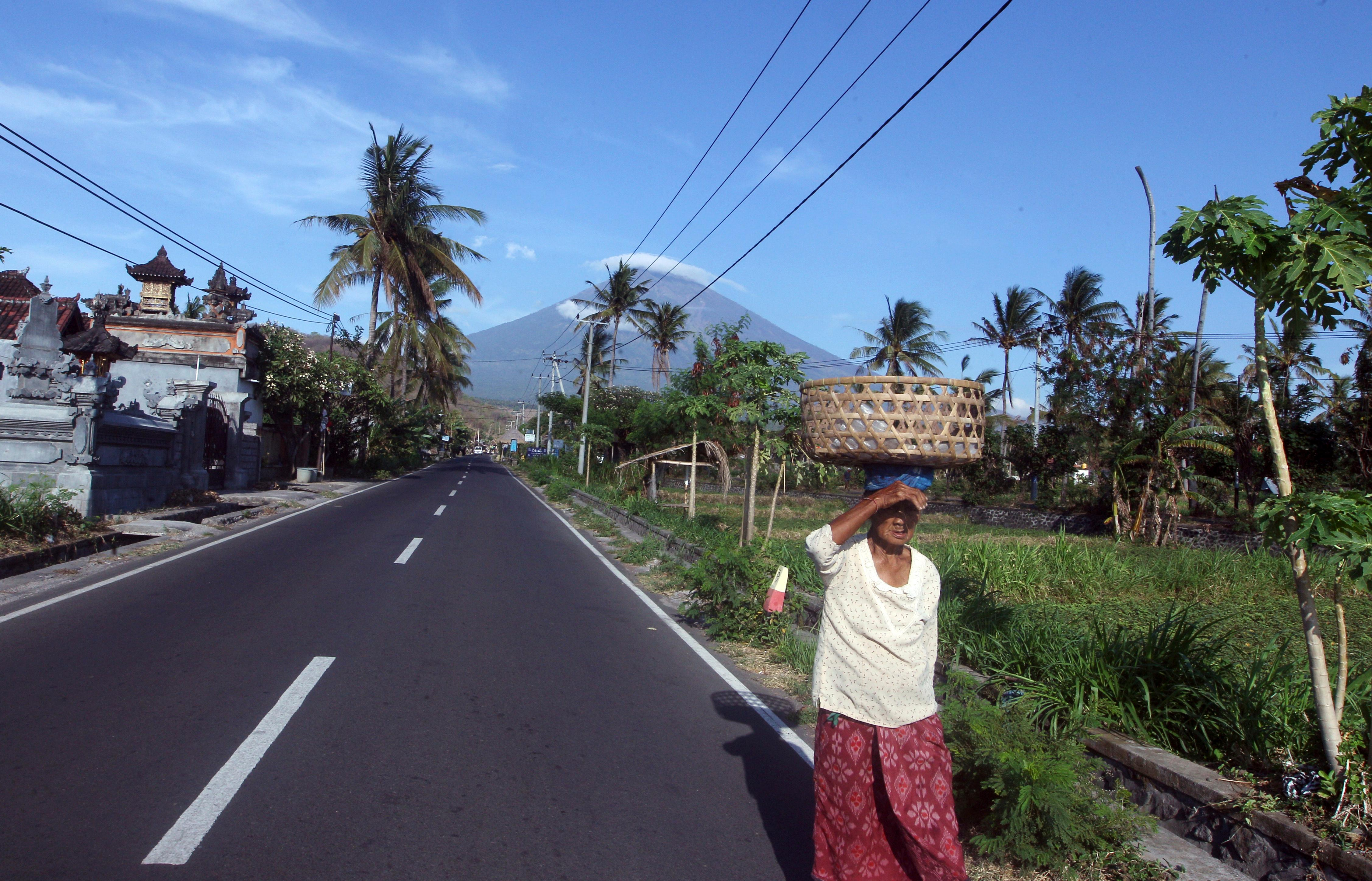 UPDATES CAPTION - A woman walks on a street with Mount Agung seen in the background in Amed, Bali, Indonesia, Tuesday, Sept. 26, 2017. More than 57,000 people have fled the surrounds of Mount Agung volcano on the Indonesian tourist island of Bali, fearing an imminent eruption, officials said Tuesday. (AP Photo/Firdia Lisnawati)