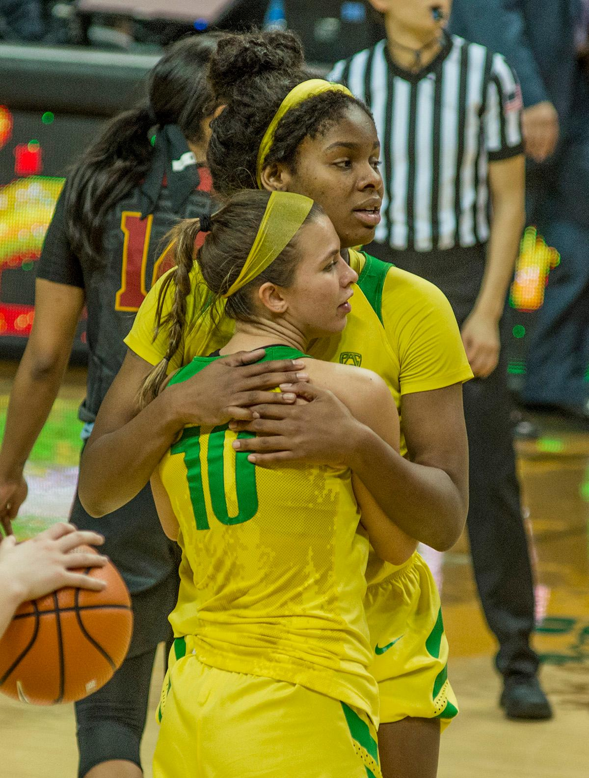 Oregon Ducks Lexi Bando (#10) and Ruthy Hebard (#24, rear) congratulate each other over their victory over the USC Trojans. The Oregon Ducks defeated the USC Trojans 80-74 on Friday at Matthew Knight Arena in a game that went into double overtime. Lexi Bando sealed the Ducks' victory by scoring a three-pointer in the closing of the game. Ruthy Hebard set a new NCAA record of 30 consecutive field goals over three games, the old record being 28. Ruthy Hebard got a double-double with 27 points and 10 rebounds, Mallory McGwire also had 10 rebounds. The Ducks had four players in double digits: Ruthy Hebard with 27; Maite Cazorla with 17; Sabrina Ionescu with 15; and Lexi Bando with 11. The Ducks are now 24-4, 13-2 in the Pac-12, and are tied for first with Stanford. Photo by Dan Morrison, Oregon News Lab