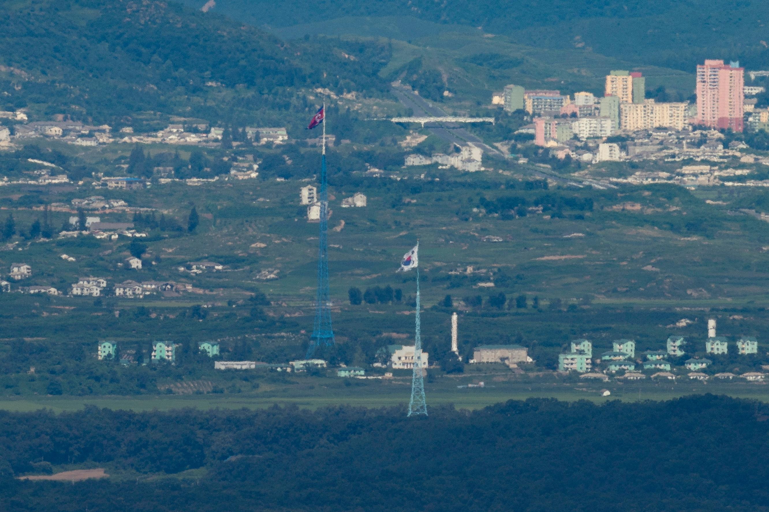 "A giant North Korean flag, left, atop a 160-meter (525-foot) tower in North Korea and a South Korean flag, right, atop of a 100-meter (328-foot) tower in South Korea, flutter in the wind as pictured from the border area between two Koreas in Paju, South Korea, Friday, Aug. 11, 2017. Not backing down, U.S. President Donald Trump warned Kim Jong Un's government on Thursday to ""get their act together"" or face extraordinary trouble, and suggested he had been too mild when he vowed to unleash ""fire and fury"" on North Korea if it continued to threaten the U.S. (Lim Byung-shik/Yonhap via AP)"