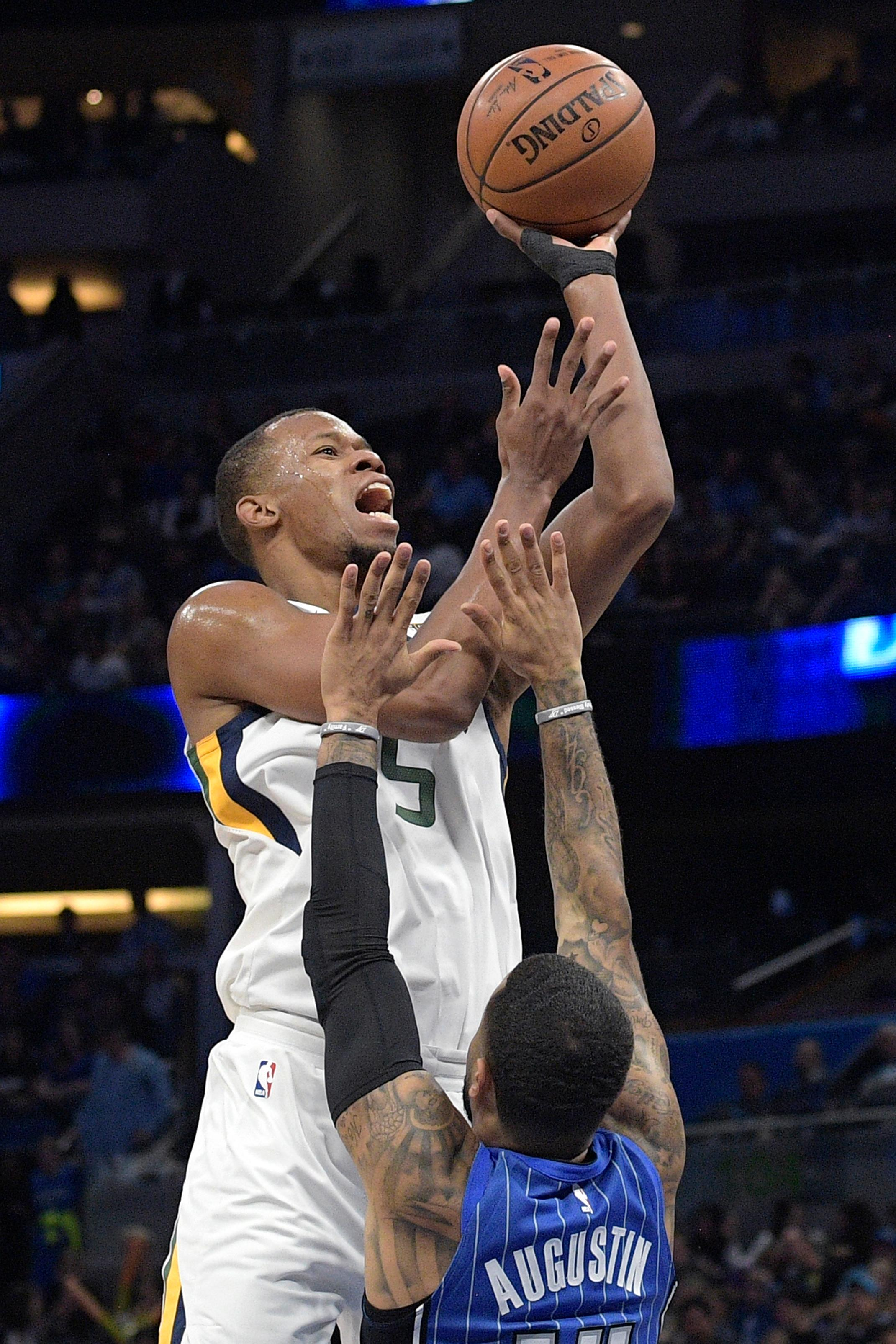 Utah Jazz guard Rodney Hood (5) goes up for a shot in front of Orlando Magic guard D.J. Augustin (14) during the first half of an NBA basketball game, Saturday, Nov. 18, 2017, in Orlando, Fla. (AP Photo/Phelan M. Ebenhack)