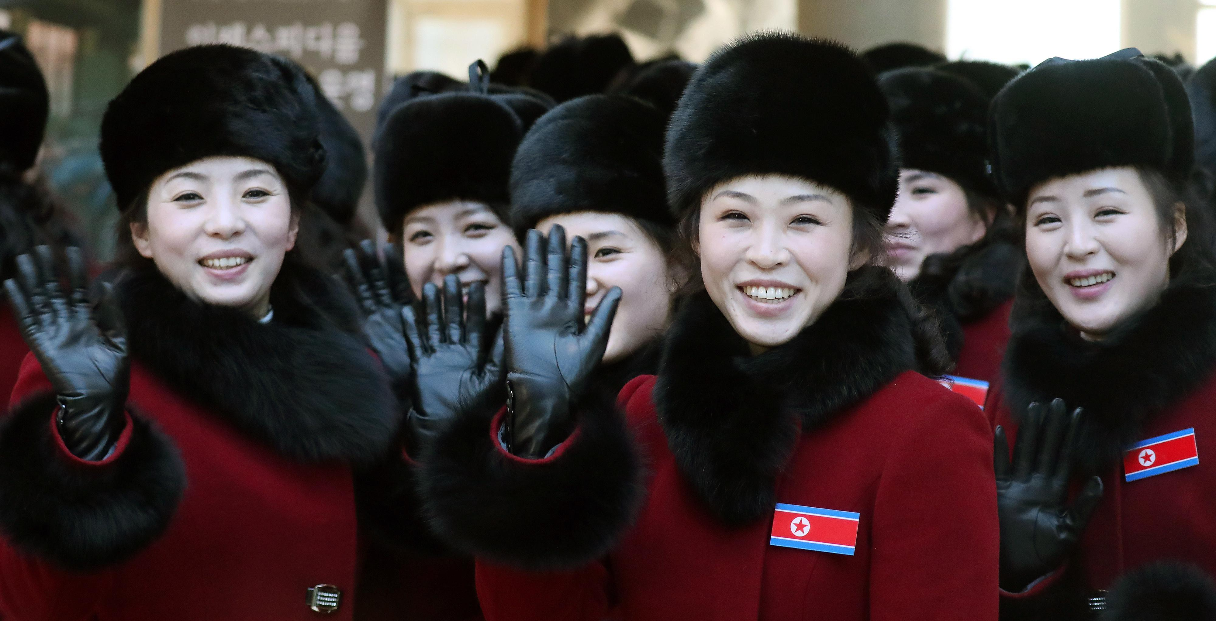 North Korean cheering squads wave upon their arrival at a stadium in Inje, South Korea, Wednesday, Feb. 7, 2018. A North Korean delegation, including members of a state-trained cheering group, arrived in South Korea on Wednesday for the Pyeongchang Winter Olympics. (Yang Yong-suk/Yonhap via AP)