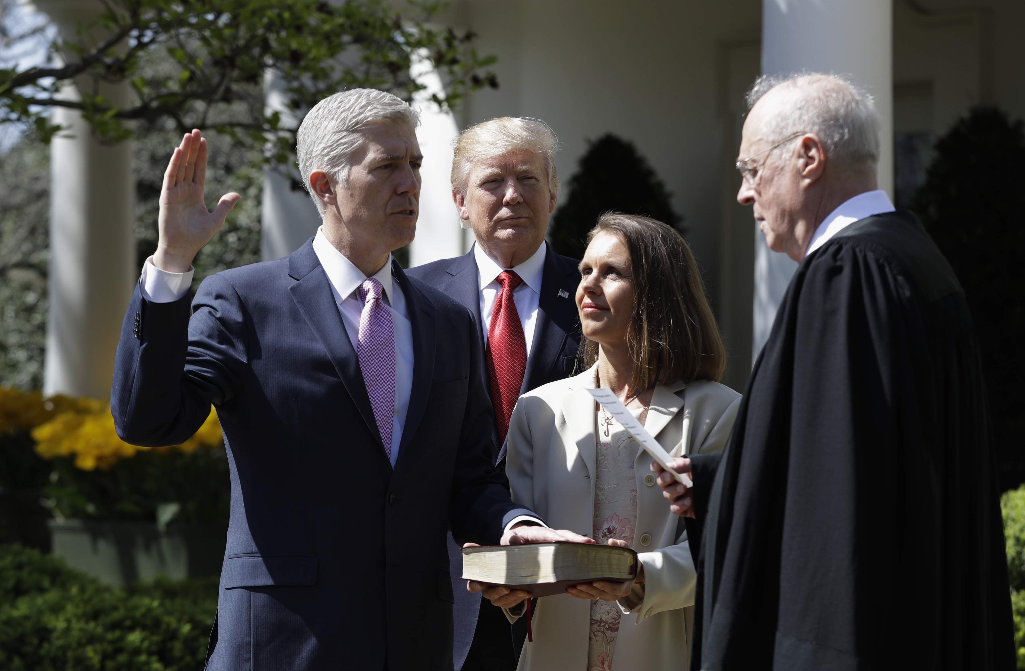 DAY 81 - In this April 10, 2017, file photo, President Donald Trump watches as Supreme Court Justice Anthony Kennedy administers the judicial oath to Justice Neil Gorsuch in the Rose Garden of the White House White House in Washington. Holding the Bible is Gorsuch's wife Marie Louise Gorsuch. (AP Photo/Evan Vucci, File)