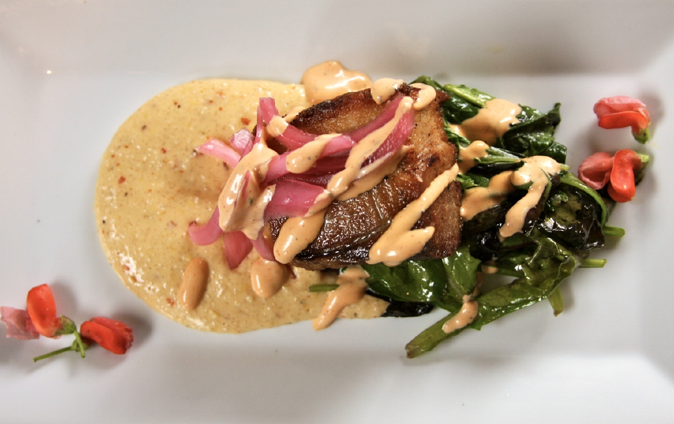 Pork Belly:  pan-seared braised pork belly, wilted greens, Aleppo and smoked cheddar grits, pickled red onion, and sriracha remoulade / Image: Molly Paz
