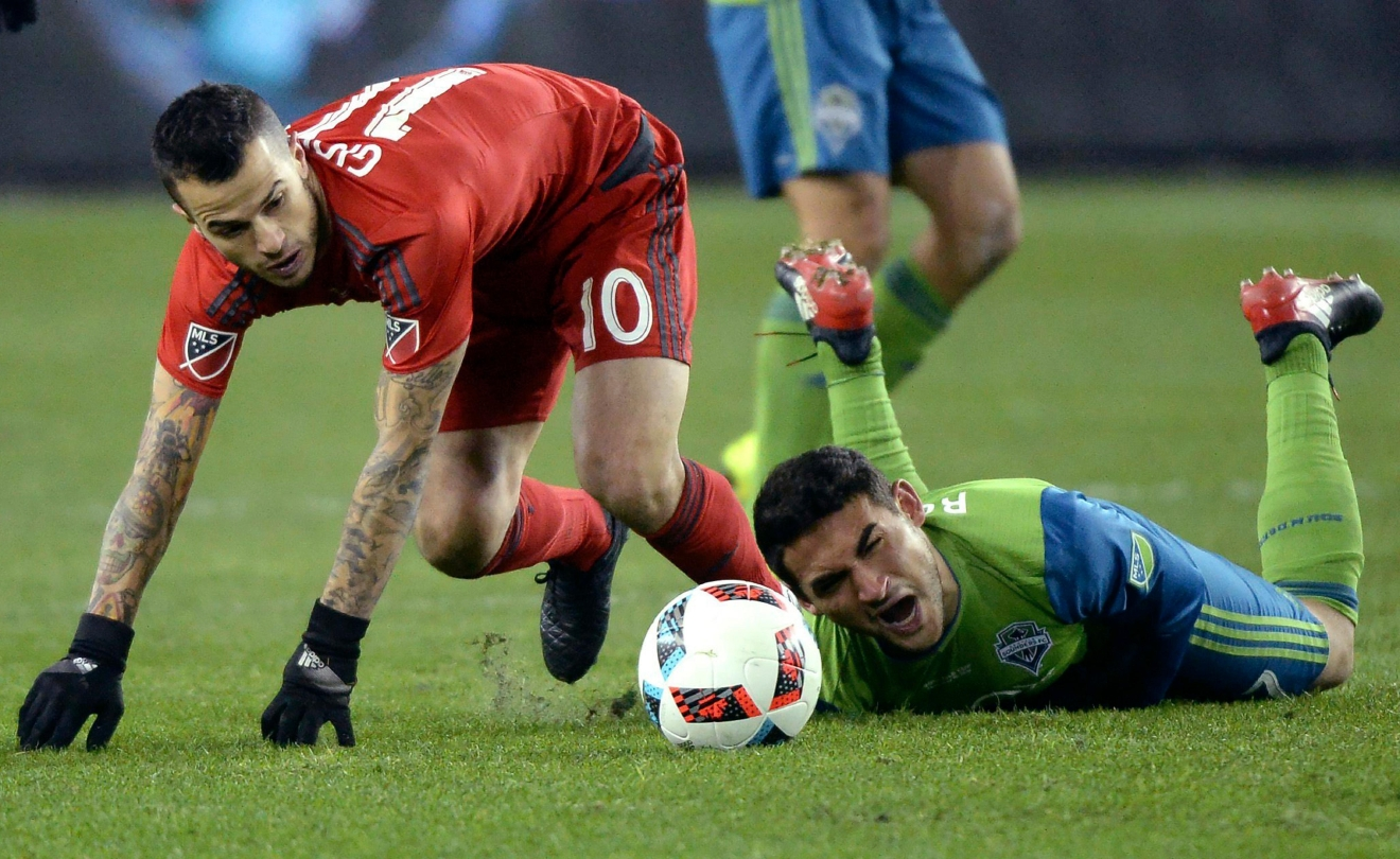 Toronto FC forward Sebastian Giovinco, left, battles Seattle Sounders midfielder Cristian Roldan during second-half MLS Cup final soccer action in Toronto, Saturday, Dec. 10, 2016. (Nathan Denette/The Canadian Press via AP)