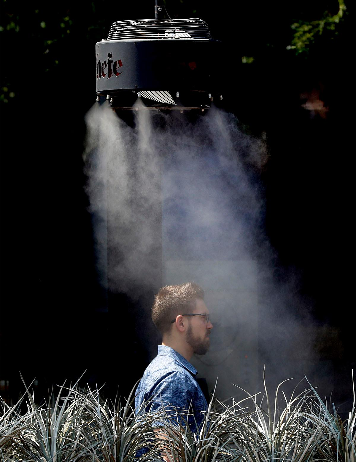 A man stands under a misting machine, Monday, June 19, 2017 in Tempe, Ariz. The forecast calls for a high of 118 on Monday and 120 on Tuesday in Phoenix. (AP Photo/Matt York)