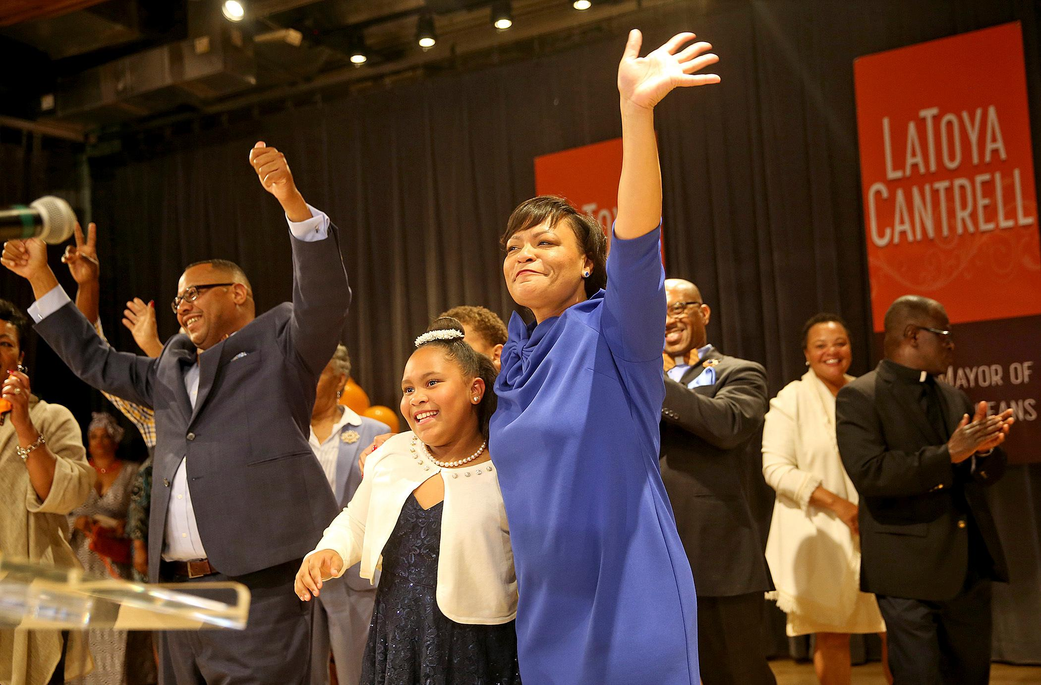 As her husband Jason Cantrell, left, cheers, LaToya Cantrell hugs her daughter RayAnn as she celebrates her victory in the New Orleans mayoral election during her election party at the New Orleans Jazz Market in Central City Saturday, Nov. 18, 2017, in New Orleans. Cantrell, a City Council member who gained a political following as she worked to help her hard-hit neighborhood recover from Hurricane Katrina, was the victor Saturday night in an election that will make her the first woman mayor in New Orleans' history. (Michael DeMocke/NOLA.com The Times-Picayune via AP)
