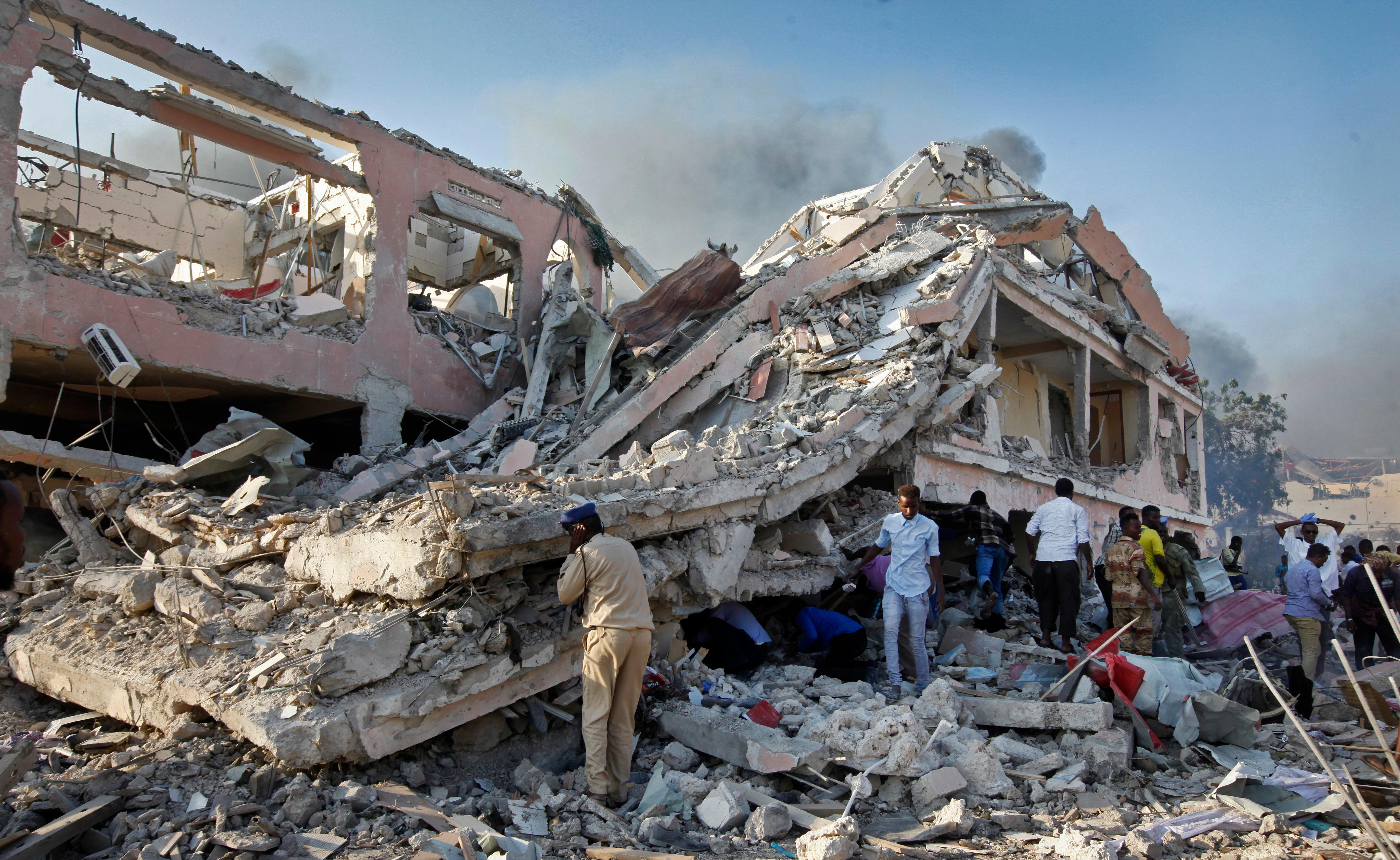 Somalis gather and search for survivors by destroyed buildings at the scene of a blast in the capital Mogadishu, Somalia Saturday, Oct. 14, 2017. A huge explosion from a truck bomb has killed at least 20 people in Somalia's capital, police said Saturday, as shaken residents called it the most powerful blast they'd heard in years. (AP Photo/Farah Abdi Warsameh)