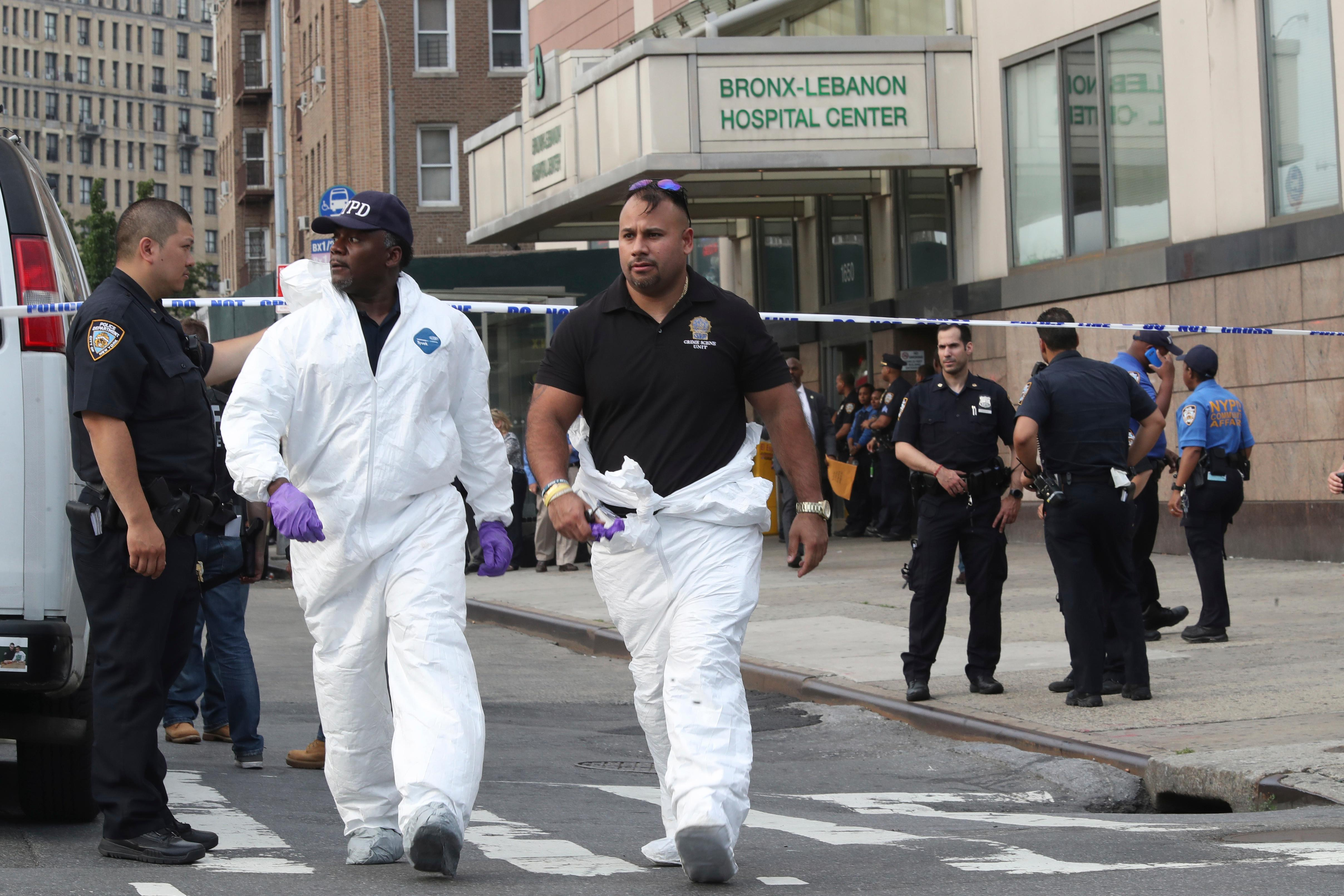 Police officers with the Forensics Unit leave Bronx Lebanon Hospital after a gunman opened fire and then took his own life there, Friday, June 30, 2017, in New York. The gunman, identified as Dr. Henry Bello who used to work at the hospital, returned with a rifle hidden under his white lab coat, law enforcement officials said. (AP Photo/Mary Altaffer)