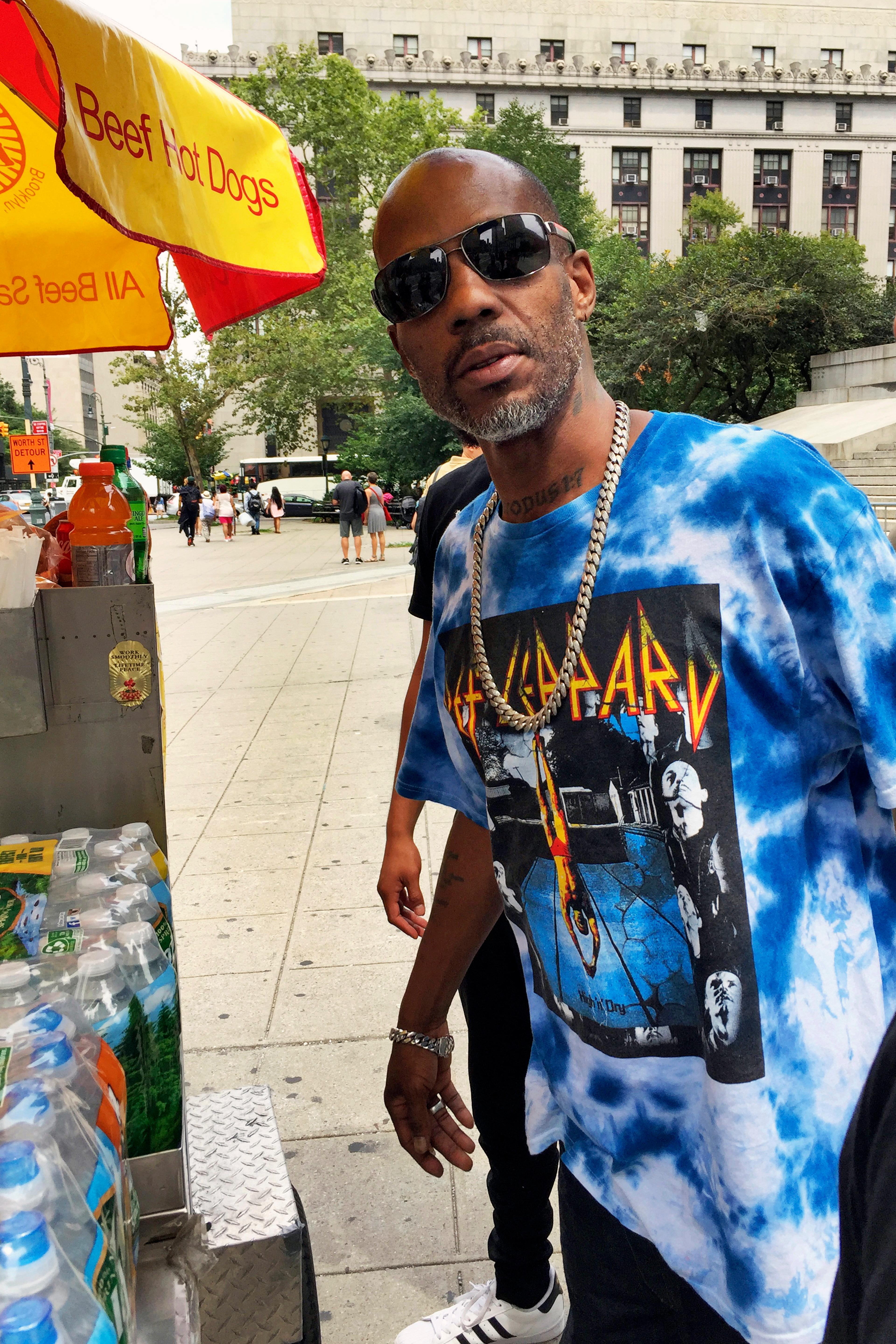 Rapper DMX, whose given name is Earl Simmons, stops to buy a hot dog outside federal court, in New York, Friday, Aug. 11, 2017. DMX, who prosecutors say owes $1.7 million in taxes, was ordered confined to his suburban New York City home Friday by a judge who said he repeatedly violated bail conditions on the tax fraud charges. (AP Photo/Larry Neumeister)