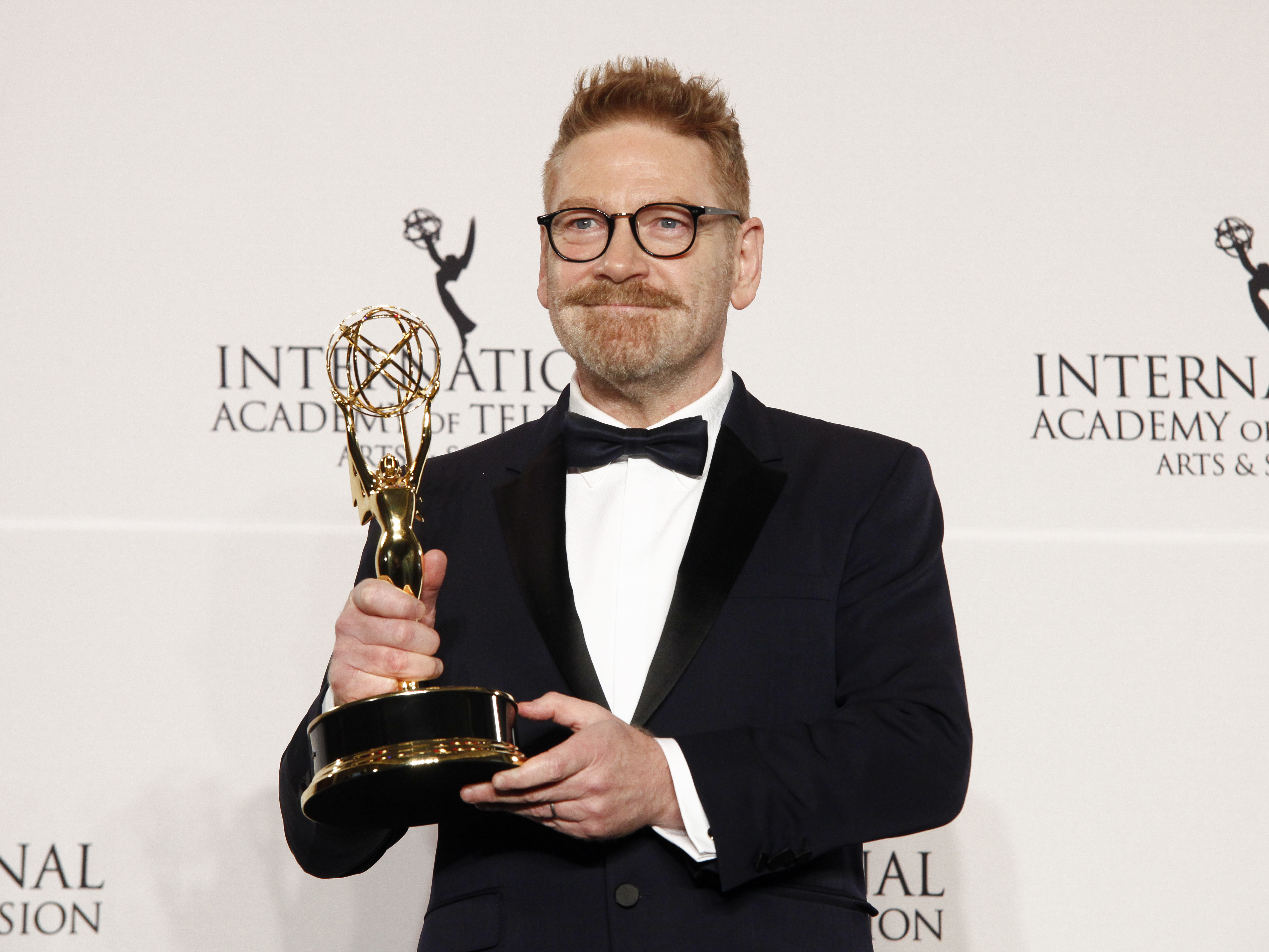 "Actor Kenneth Branagh poses in the pressroom with the award for best performance by an actor in ""Wallander"" at the at the New York Hilton on Monday, Nov. 20, 2017, in New York. (Photo by Andy Kropa/Invision/AP)"