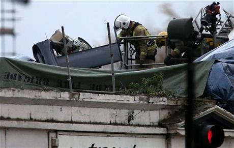 Scottish Fire and Rescue services look at the exposed part of the helicopter tail fin and rotor at the scene on Saturday, Nov. 30, 2013, following the helicopter crash at the Clutha Bar in Glasgow, Scotland.