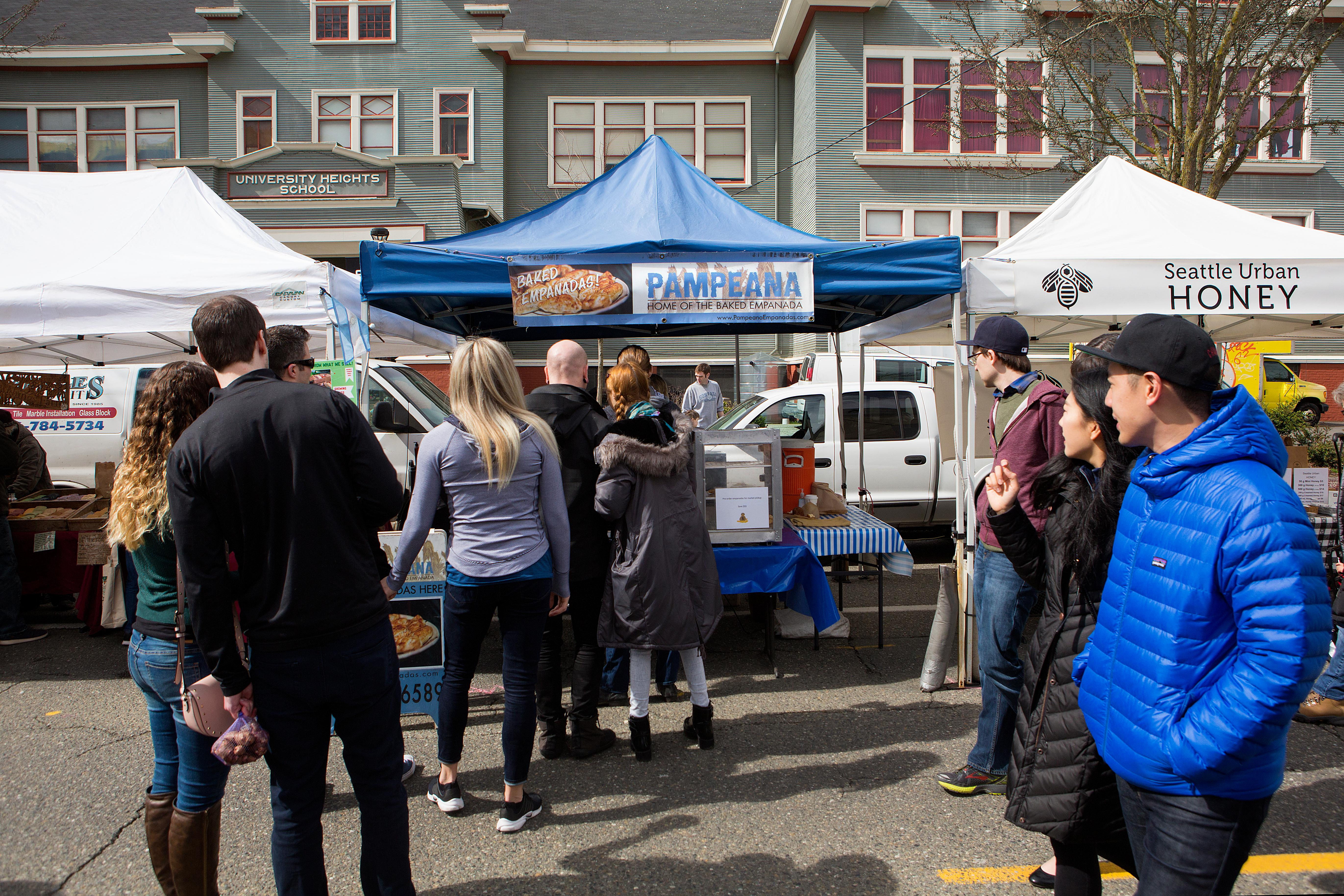 Pampeana Empanada co-owner Nancy Oltman serves up freshly baked empanadas at her booth at the U-District Farmers market. The empanadas come in various flavors, such as spinach and cheese, beef, chicken, and Beecher's mac and cheese. The Tacoma based business sells their baked goods at the U-District and Proctor farmers markets, the West Seattle Thriftway, and at various Metropolitan Market locations. (Sy Bean / Seattle Refined)