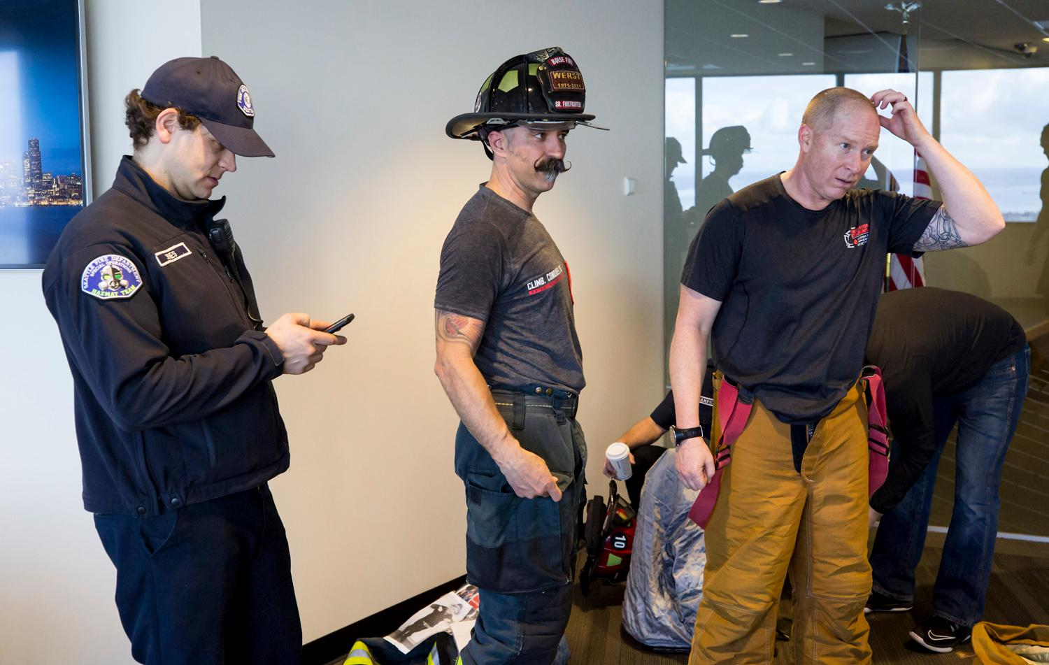 Rich Brown, center, and Dave O'Connor, both firefighters from Boise, Idaho, take a breather after completing a training climb for the 27th annual Scott Firefight Stairclimb that benefits the Leukemia & Lymphoma Society. 2,000 firefighters will climb the 69 floors (1,356 stairs!) on Sunday to Sky View Observatory of the Columbia Tower. To donate to this cause, please visit www.firefighterstairclimb.org. (Sy Bean / Seattle Refined)
