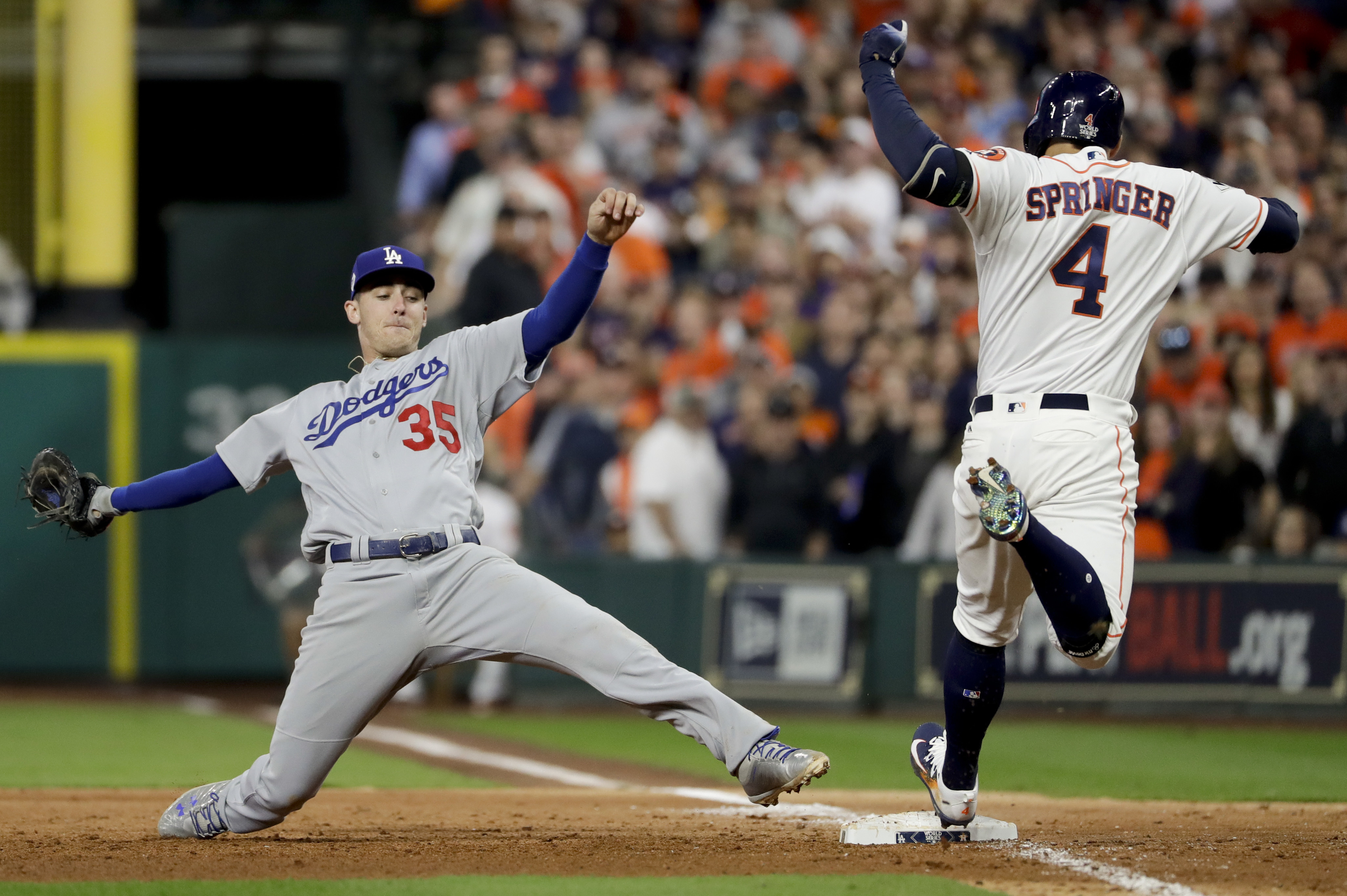 Houston Astros' George Springer beats Los Angeles Dodgers' Cody Bellinger to first base during the sixth inning of Game 3 of baseball's World Series Friday, Oct. 27, 2017, in Houston. (AP Photo/Matt Slocum)