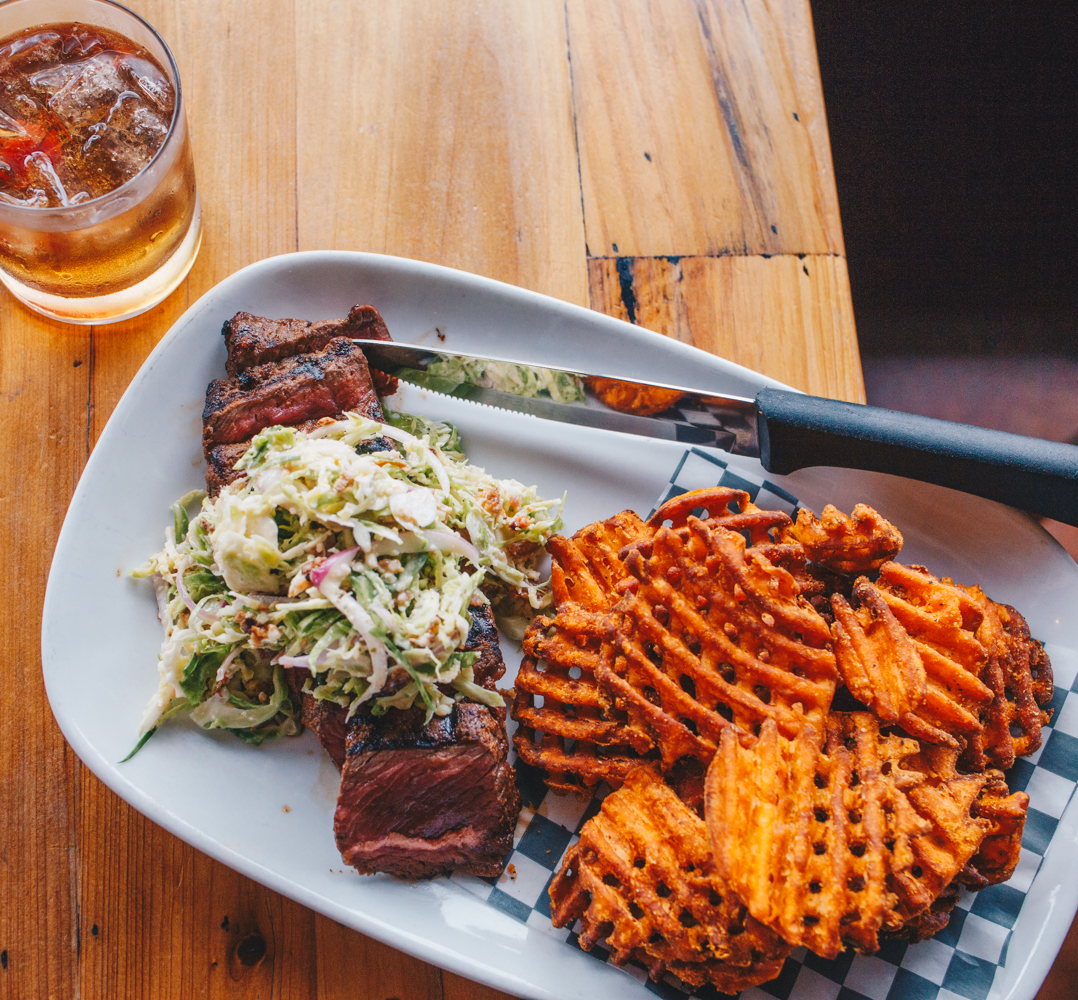 Charbroiled sirloin with shaved brussel sprout-bacon-shallot salad and sweet potato waffle fries, served with the Belly Up cocktail / Image: Catherine Viox // Published: 10.17.18