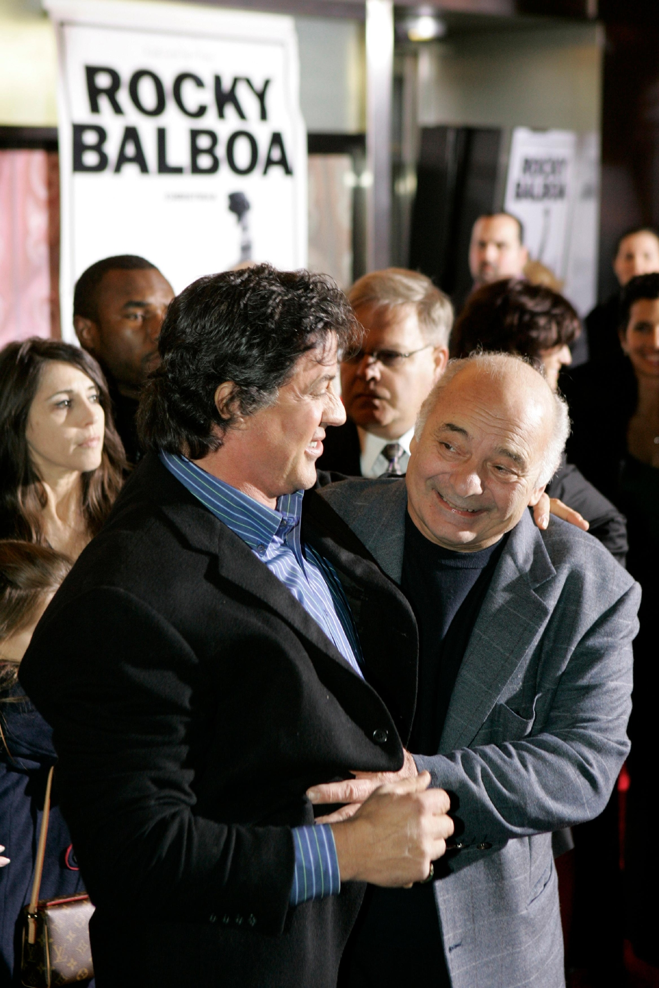 "FILE – In this Dec. 18, 2006, file photo, actor and screenwriter Sylvester Stallone, left, and his ""Rocky"" co-star Burt Young, right, attend a premiere of the movie ""Rocky Balboa"" in Philadelphia. Four decades after the Nov. 21, 1976, premiere of ""Rocky,"" the movie's reach is international, and the title character's underdog tale of determination, grit and sleepy-eyed charm still resonates with fans. (AP Photo/Matt Rourke, File)"