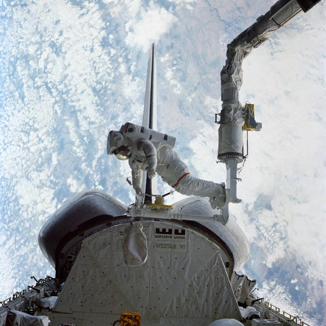 <p>Astronaut Bruce McCandless II, STS-41B mission specialist, tests a &quot;cherry-picker&quot; type device during the Feb. 7, 1984, historic spacewalk. The spacewalk, in which Astronauts McCandless and Robert L. Stewart participated, marked two firsts--initial use of both the Mobile Foot Restraint (MFR) attached to the Remote Manipulator System (RMS) arm here, and the Manned Maneuvering Unit (MMU) backpack. The space shuttle Challenger was flying with its aft end aimed toward the Earth. This photograph clearly shows where the MFR connects to the end effector of the Canadian-built RMS arm. The two spacewalkers were monitored and photographed by their fellow crewmembers, astronauts Vance D. Brand, commander; Robert L. Gibson, pilot; and Ronald E. McNair, mission specialist. The three remained in the cabin for another spacewalk two days later. (Image Credit: NASA)</p>