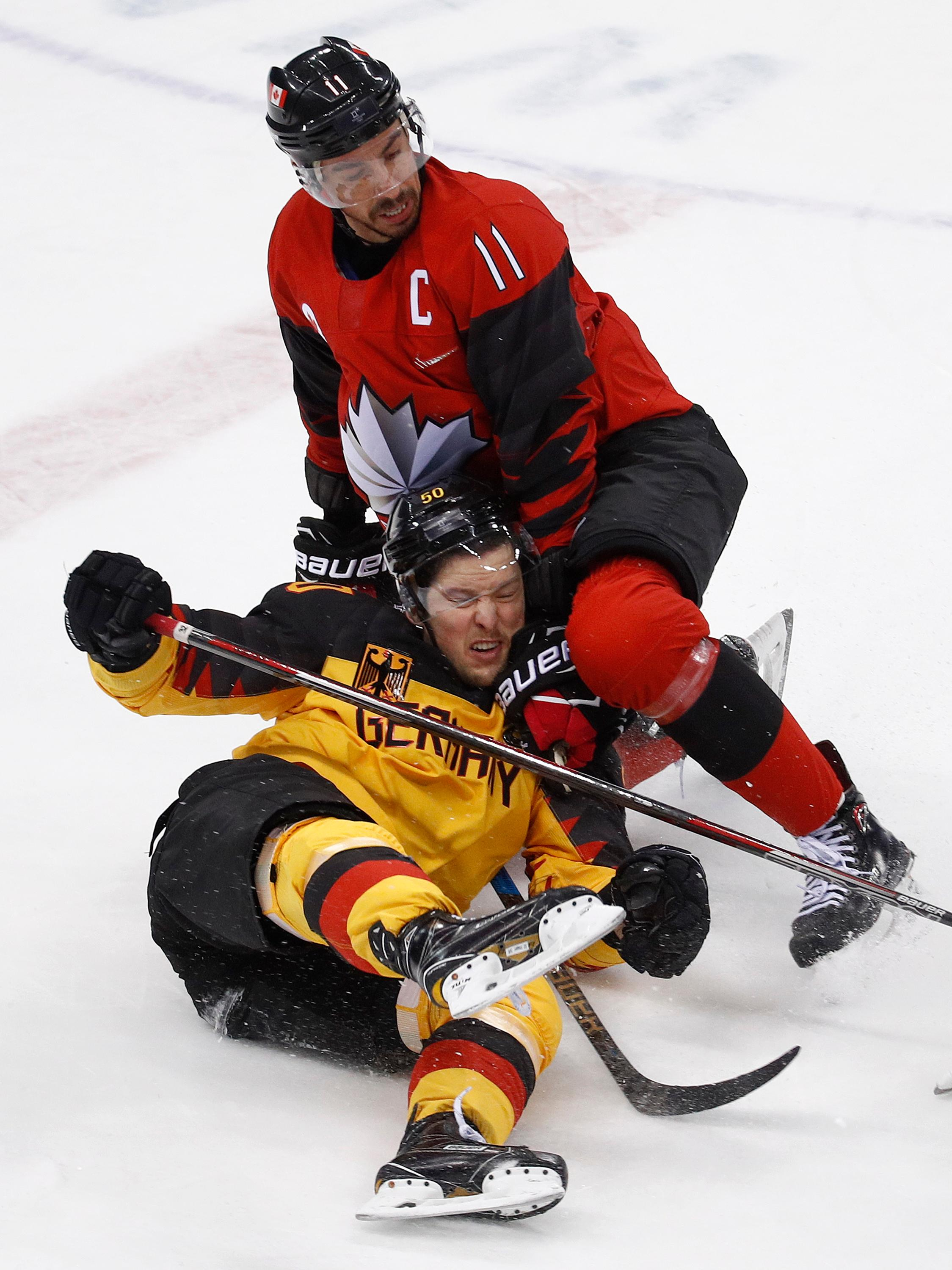 Chris Kelly (11), of Canada, checks Patrick Hager (50), of Germany, during the first period of the semifinal round of the men's hockey game at the 2018 Winter Olympics in Gangneung, South Korea, Friday, Feb. 23, 2018. (AP Photo/Patrick Semansky)