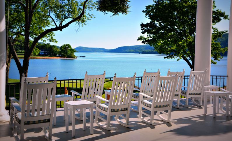 Afterwards, sip a drink on a porch rocking chair overlooking the lake.{ } (Image: Courtesy The Otesaga Resort)