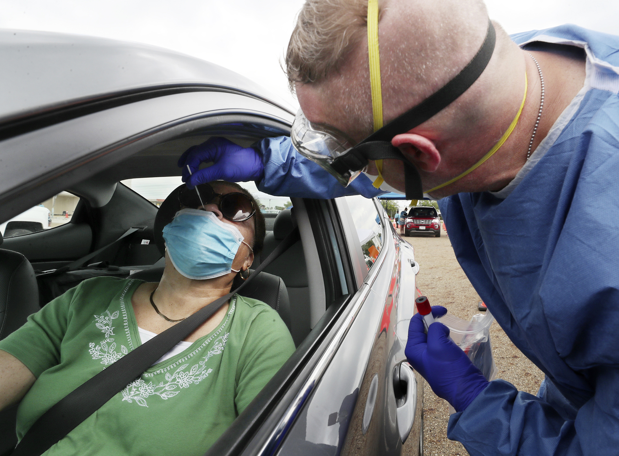 An Ohio National Guard Medic tests Elizabeth England in her car at a Summit County Department of Health COVID-19 testing site at Chapel Hill Mall on Saturday, Sept. 12, 2020, in Akron, Ohio. Hospitals around the United States are starting to buckle from a resurgence of COVID-19 cases, with several states setting records for the number of people hospitalized and leaders scrambling to find extra beds and staff. New highs in cases have been reported in states big and small, from Idaho to Ohio. (Mike Cardew/Akron Beacon Journal via AP)