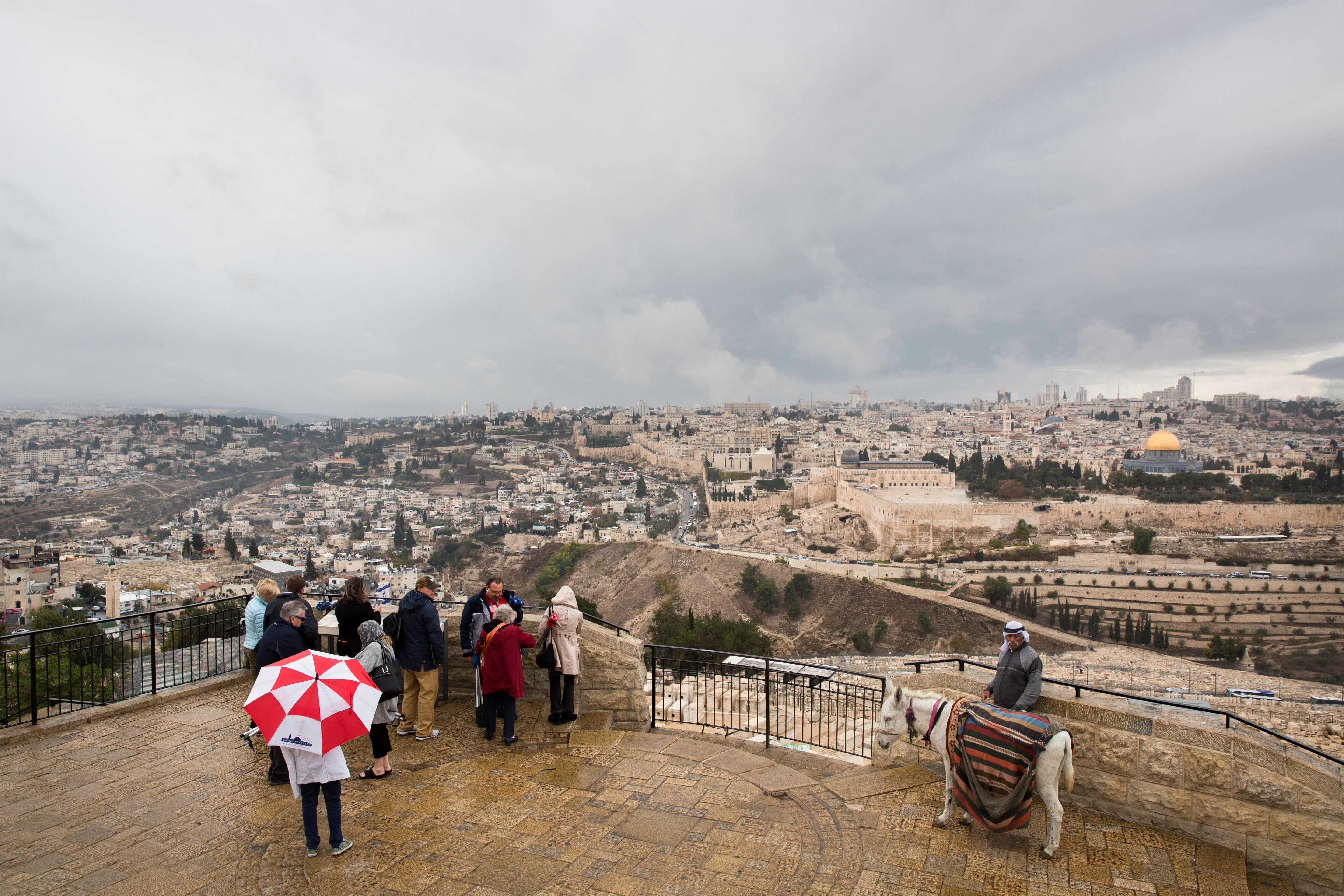 A group of tourists visit Mount of Olives overlooking the Old City in Jerusalem, Wednesday, Dec. 6, 2017. U.S. officials say President Donald Trump will recognize Jerusalem as Israel's capital Wednesday, Dec. 6, and instruct the State Department to begin the multi-year process of moving the American embassy from Tel Aviv to the holy city. His decision could have deep repercussions across the region. (AP Photo/Oded Balilty)