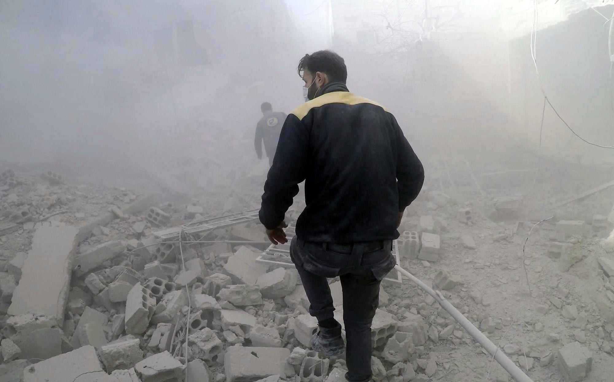 This photo provided by the Syrian Civil Defense White Helmets, which has been authenticated based on its contents and other AP reporting, shows civil defense workers searching for survivors after airstrikes hit a rebel-held suburb near Damascus, Syria, Thursday, Feb. 8, 2018. Syrian rescue workers and activists say the death toll from ongoing government strikes on the opposition-held region near the capital Damascus has risen to at least 35. (Syrian Civil Defense White Helmets via AP)