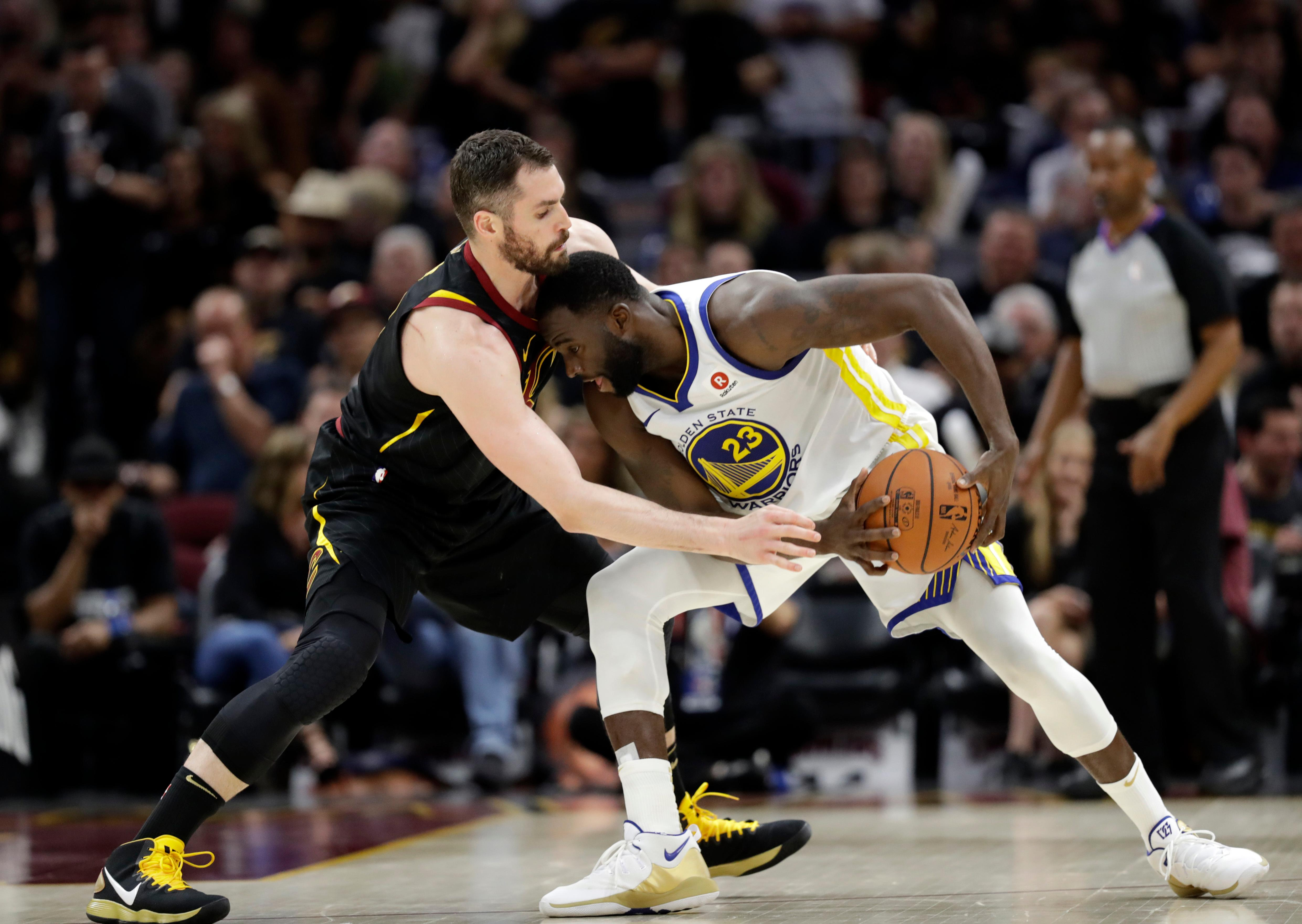 Golden State Warriors' Draymond Green is defended by Cleveland Cavaliers' Kevin Love during the second half of Game 4 of basketball's NBA Finals, Friday, June 8, 2018, in Cleveland. (AP Photo/Tony Dejak)
