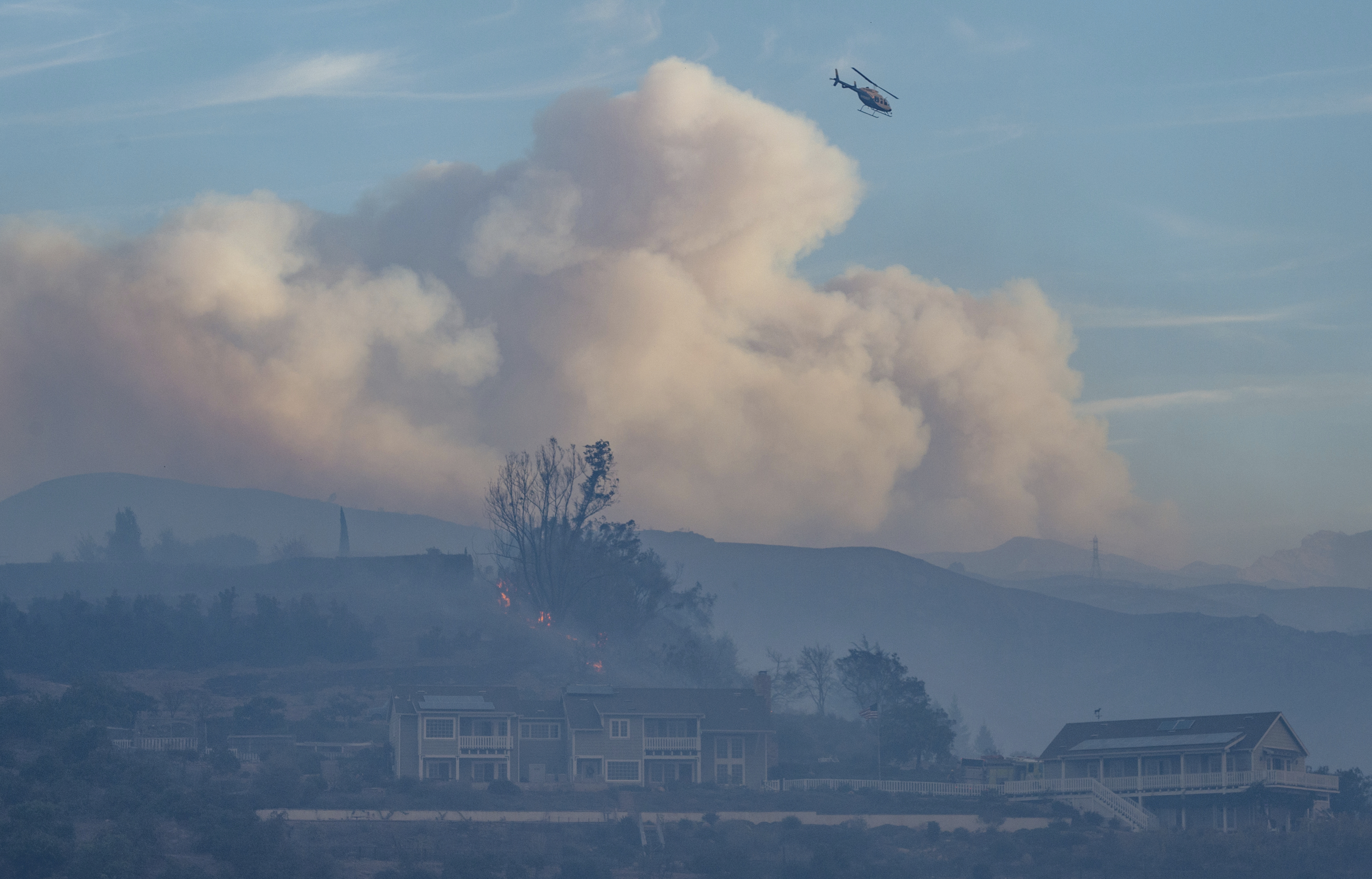 In this Sunday, Dec. 10, 2017, photo clouds form in the distance as two homes stay standing after surviving an early morning wildfire at the Shepard Mesa neighborhood in Carpinteria, Calif. (Kenneth Song/Santa Barbara News-Press via AP)