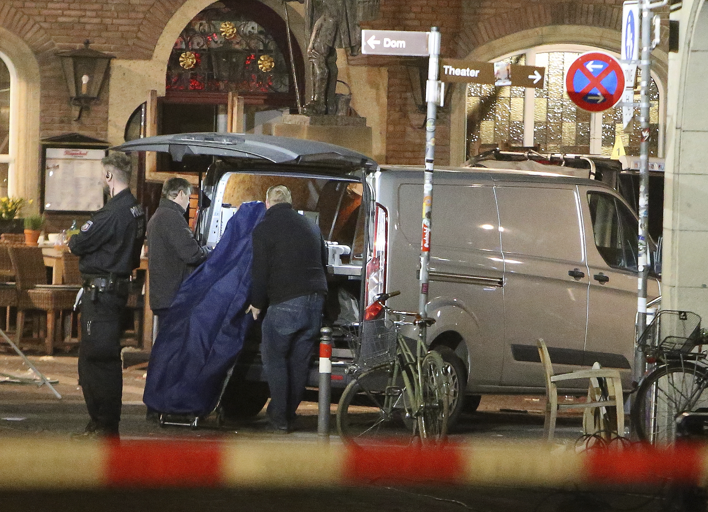 A body is loaded into a vehicle in front of a restaurant in Muenster, Germany, Sunday, April 8, 2018 after a vehicle crashed into a crowd. A van crashed into people drinking outside a popular bar Saturday in the German city of Muenster, killing two people and injuring 20 others before the driver of the vehicle shot and killed himself inside it, police said. (David Young/dpa via AP)