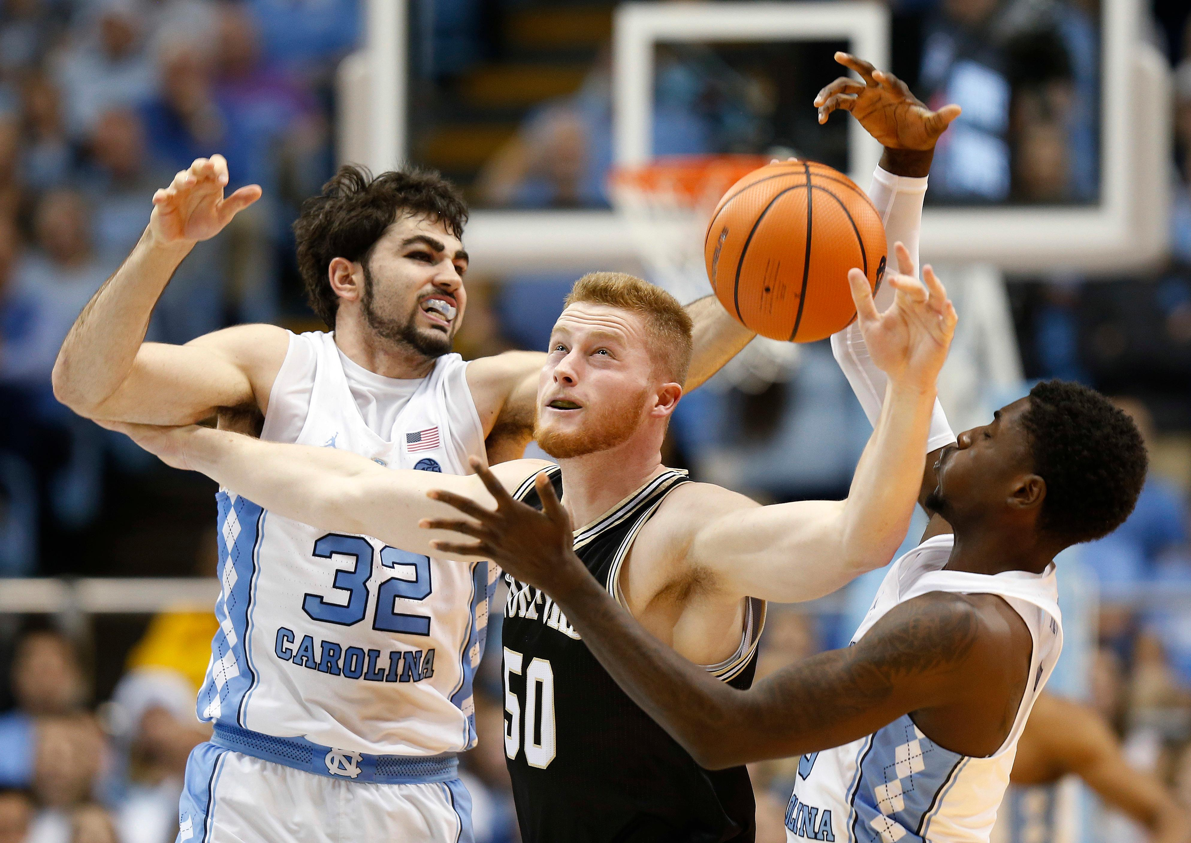 North Carolina forward Luke Maye (32) and teammate North Carolina guard Jalek Felton (5) battle Wofford center Matthew Pegram for a loose ball during the first half of an NCAA college basketball game in Chapel Hill, N.C., Wednesday, Dec. 20, 2017. (AP Photo/Ellen Ozier)