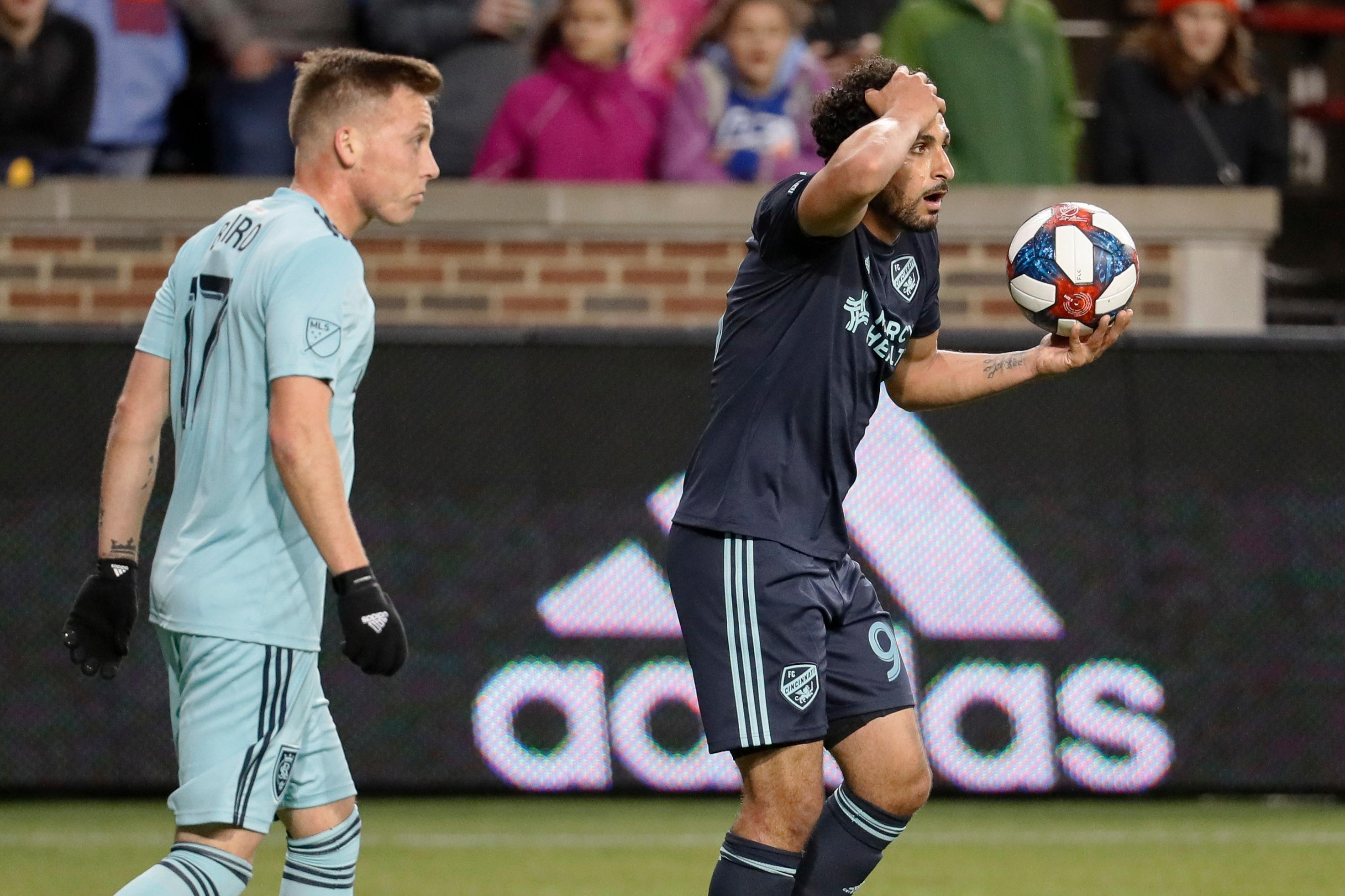 FC Cincinnati midfielder Kenny Saief, right, reacts alongside Real Salt Lake forward Corey Baird (17) during the first half of an MLS soccer match Friday, April 19, 2019, in Cincinnati. (AP Photo/John Minchillo)