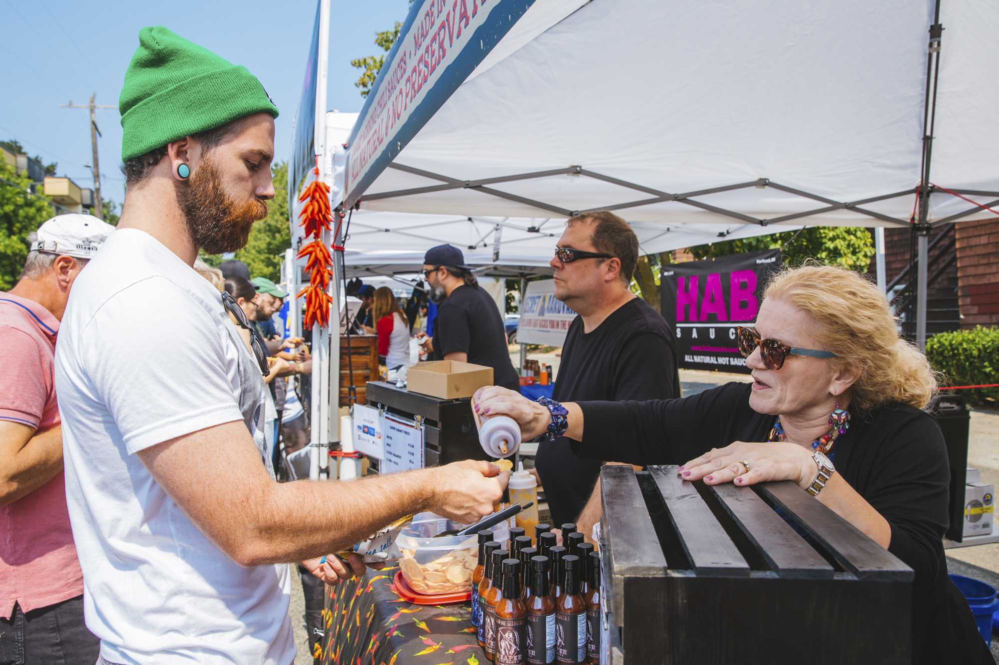 Seattle's *hottest* festival popped up this Saturday, August 18 at Ballard Commons Park and it was hot, hot, HOT! The Hot Sauce Fest featured some of the best hot sauces, food trucks and entertainment. Festival goers washed down the hot sauce burn with beers from Diamond Knot Craft Brewing and cocktails from Heritage Distilling Company (Image: Sunita Martini / Seattle Refined).