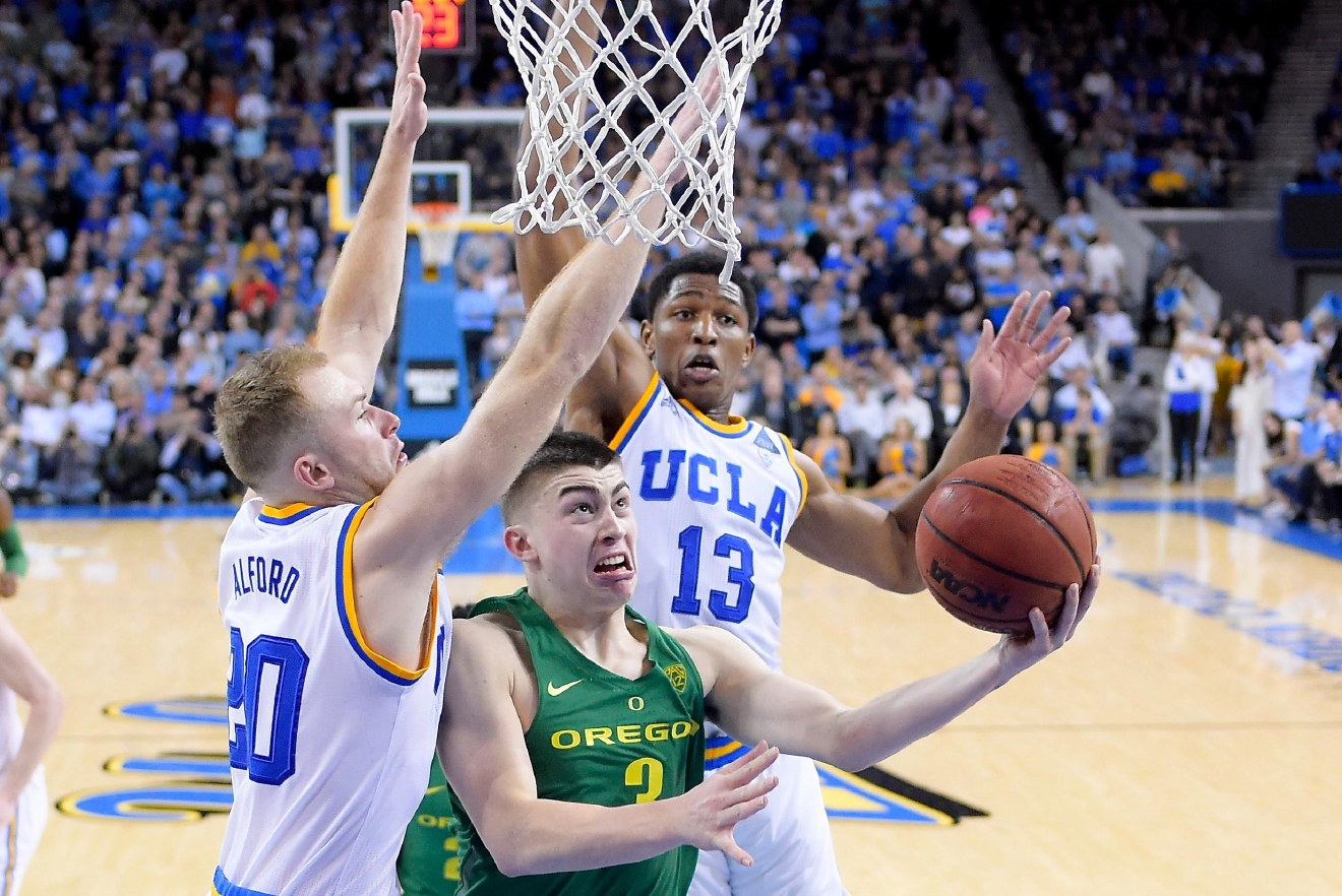 Oregon guard Payton Pritchard, center, shoots as UCLA guard Bryce Alford, left, and forward Ike Anigbogu defend during the second half of an NCAA college basketball game, Thursday, Feb. 9, 2017, in Los Angeles. UCLA won 82-79. (AP Photo/Mark J. Terrill)