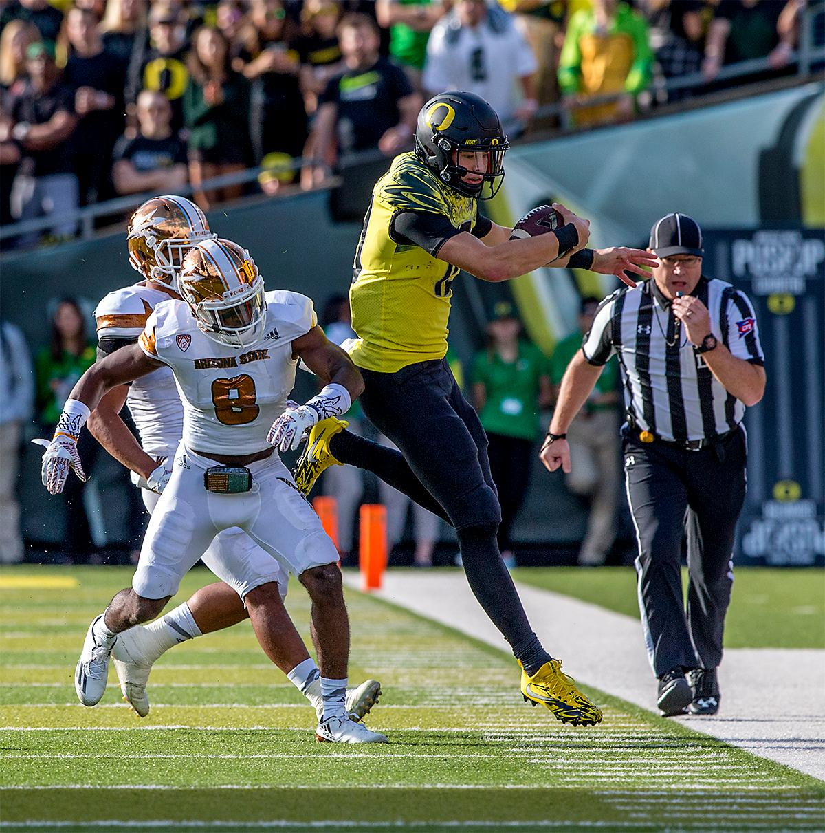 The Duck's Justin Herbert (#10) is pushed out of bounds by the Sun Devils' De'Chavon Gump Hayes (#8). The Oregon Ducks broke their losing streak by defeating the ASU Sun Devils on Saturday 54-35. Photo by August Frank, Oregon News Lab