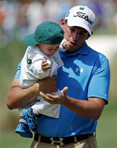 Scott Stallings gets a golf ball from his son Finn during the par three competition at the Masters golf tournament Wednesday, April 9, 2014, in Augusta, Ga.