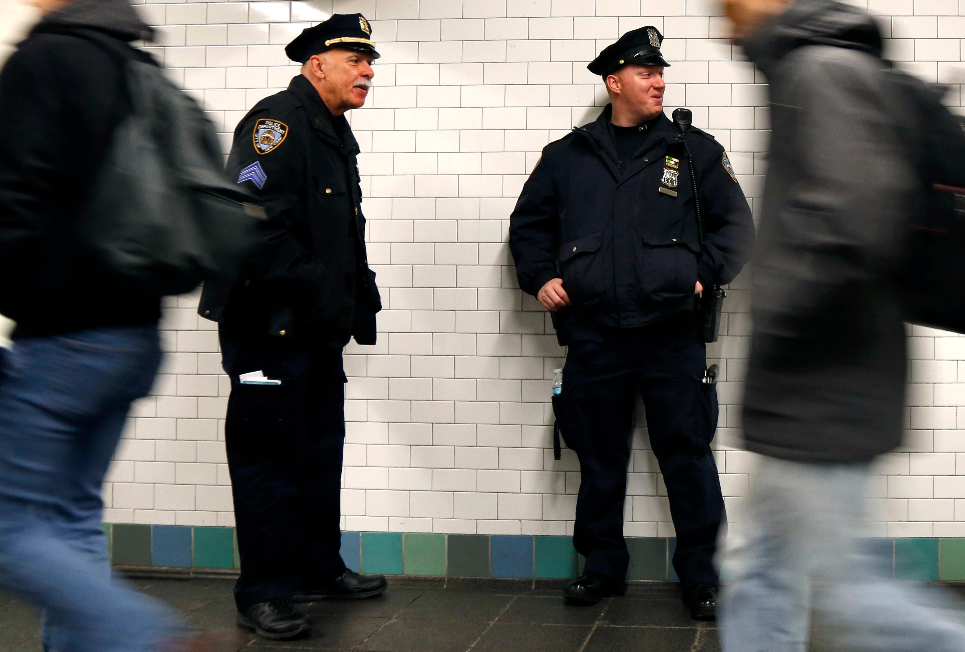 Police officers patrol in the passageway connecting New York City's Port Authority bus terminal and the Times Square subway station Tuesday, Dec. 12, 2017, near the site of Monday's explosion. Commuters returning to New York City's subway system on Tuesday were met with heightened security a day after a would-be suicide bomber's rush-hour blast failed to cause the bloodshed he intended. (AP Photo/Seth Wenig)