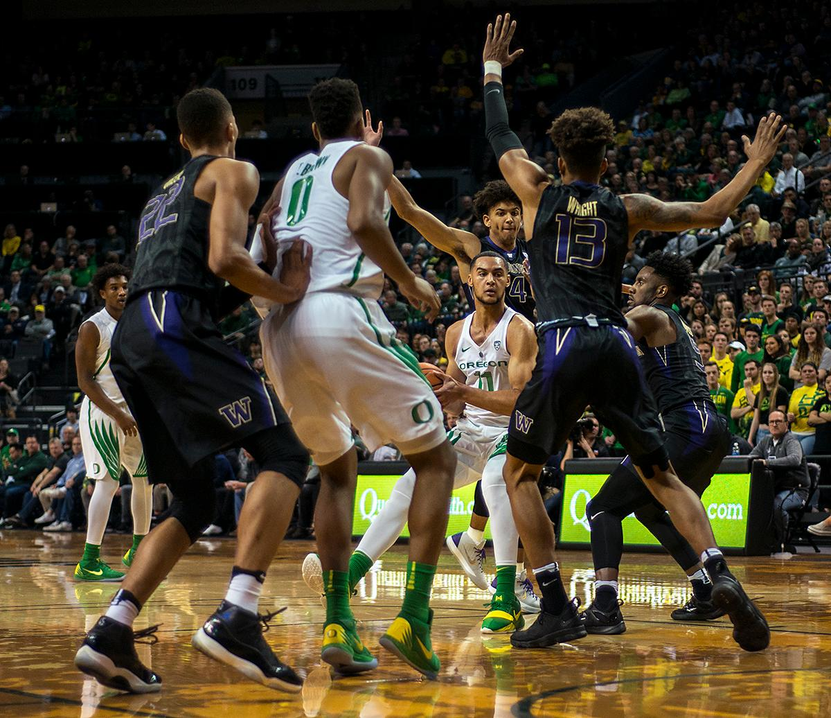 Oregon Ducks forward Keith Smith (#11) is surrounded by the Huskies defense as his team tries to continue the play. The Oregon Ducks defeated the Washington Huskies 65-40 on Thursday night at Matthew Knight Arena. Troy Brown, Junior led Oregon with 21 points to match his career high, and Kenny Wooten set a career best of seven shots blocked. The Ducks now stand 6-5 in the Pac-12 conference play. Photo by Abigail Winn, Oregon News Lab