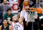 Toronto Raptors center Jonas Valanciunas (17) dunks as Milwaukee Bucks forward Giannis Antetokounmpo (34) looks on during the second half in Game 5 of a first-round NBA playoff series in Toronto on Monday, April 24, 2017.
