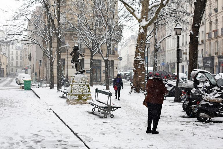 People walk in a snowy street of Paris, Friday, Feb. 9, 2018. Authorities are telling drivers in the Paris region to stay home as snow and freezing rain have hit a swath of France ill-prepared for the wintry weather. (AP Photo/Thibault Camus)