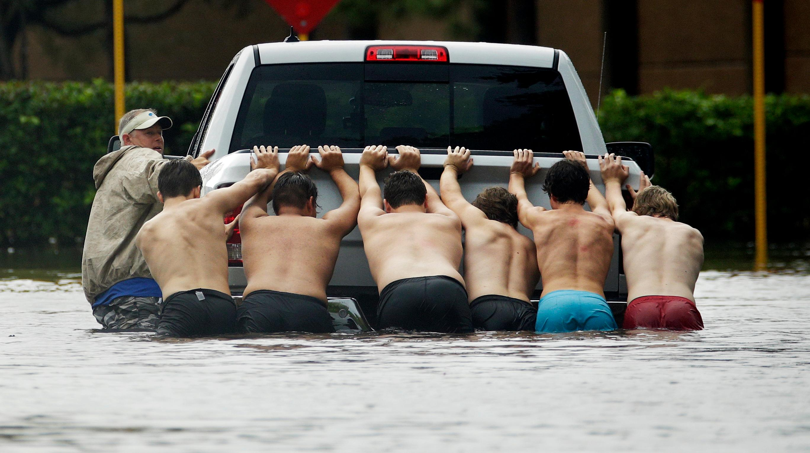 People push a stalled pickup through a flooded street in Houston, after Tropical Storm Harvey dumped heavy rains, Sunday, Aug. 27, 2017. The remnants of Harvey sent devastating floods pouring into Houston on Sunday as rising water chased thousands of people to rooftops or higher ground. (AP Photo/Charlie Riedel)