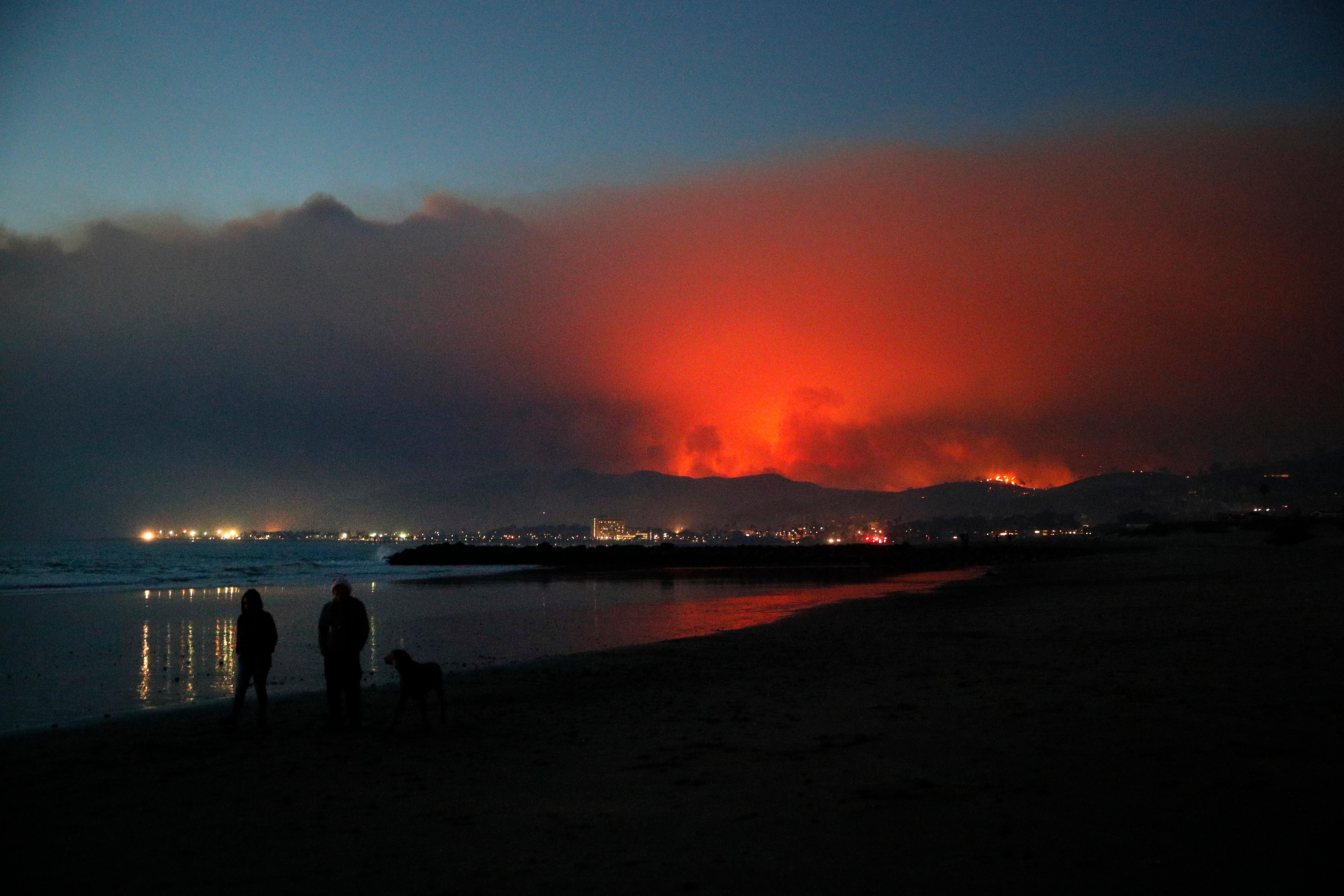 Two people walk along the beach with a dog as a wildfire burns in distance Tuesday, Dec. 5, 2017, in Ventura, Calif. Raked by ferocious Santa Ana winds, explosive wildfires northwest of Los Angeles and in the city's foothills burned a psychiatric hospital and scores of homes Tuesday and forced the evacuation of tens of thousands of people. (AP Photo/Jae C. Hong)