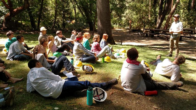 Photo by Maureen Battistella<br>At the end of a long day of work, the interns relax in the shade and learn from scientists and other professionals working in natural resources. Sean Prive, a restoration ecologist with Lomakatsi talks with Thursday's interns.