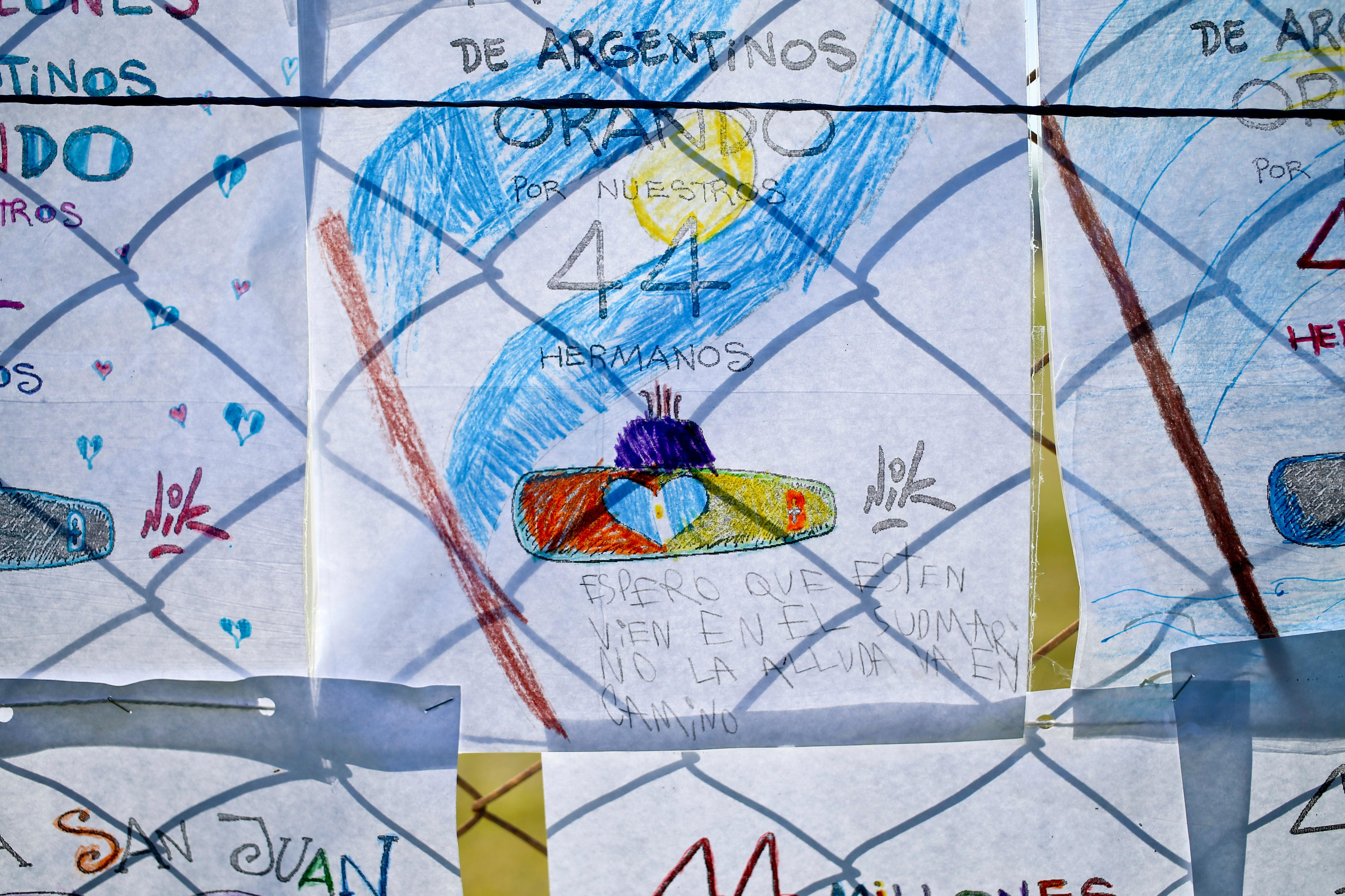 Children's drawings depicting the missing ARA San Juan submarine blanket hang on a fence enclosing the Mar de Plata Naval Base, in Argentina, Thursday, Nov. 23, 2017. A Navy spokesman said that the relatives of the crew have been informed that a sound detected during the search for the missing ARA San Juan submarine is consistent with that of an explosion, and that the search will continue until there is full certainty about the fate of the submarine. (AP Photo/Esteban Felix)