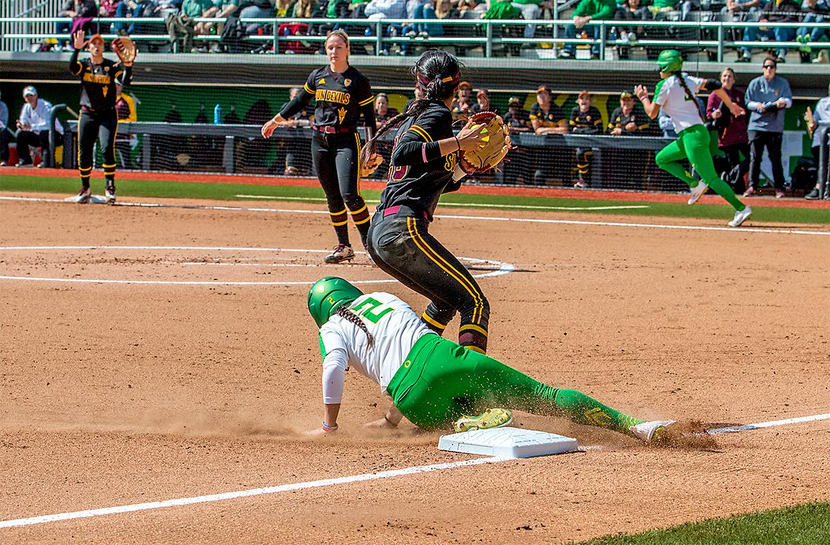 The Duck's Danica Mercado (#2) slides into third too late as the Sun Devils' Taylor Becerra (#26) prepares to throw to first base. The Oregon Ducks Softball team took their third win over the Arizona Sun Devils, 1-0, in the final game of the weekends series that saw the game go into an eighth inning before the Duck?s Mia Camuso (#7) scored a hit allowing teammate Haley Cruse (#26) to run into home plate for a point. The Ducks are now 33-0 this season and will next play a double header against Portland State on Tuesday, April 4 at Jane Sanders Stadium. Photo by August Frank, Oregon News Lab