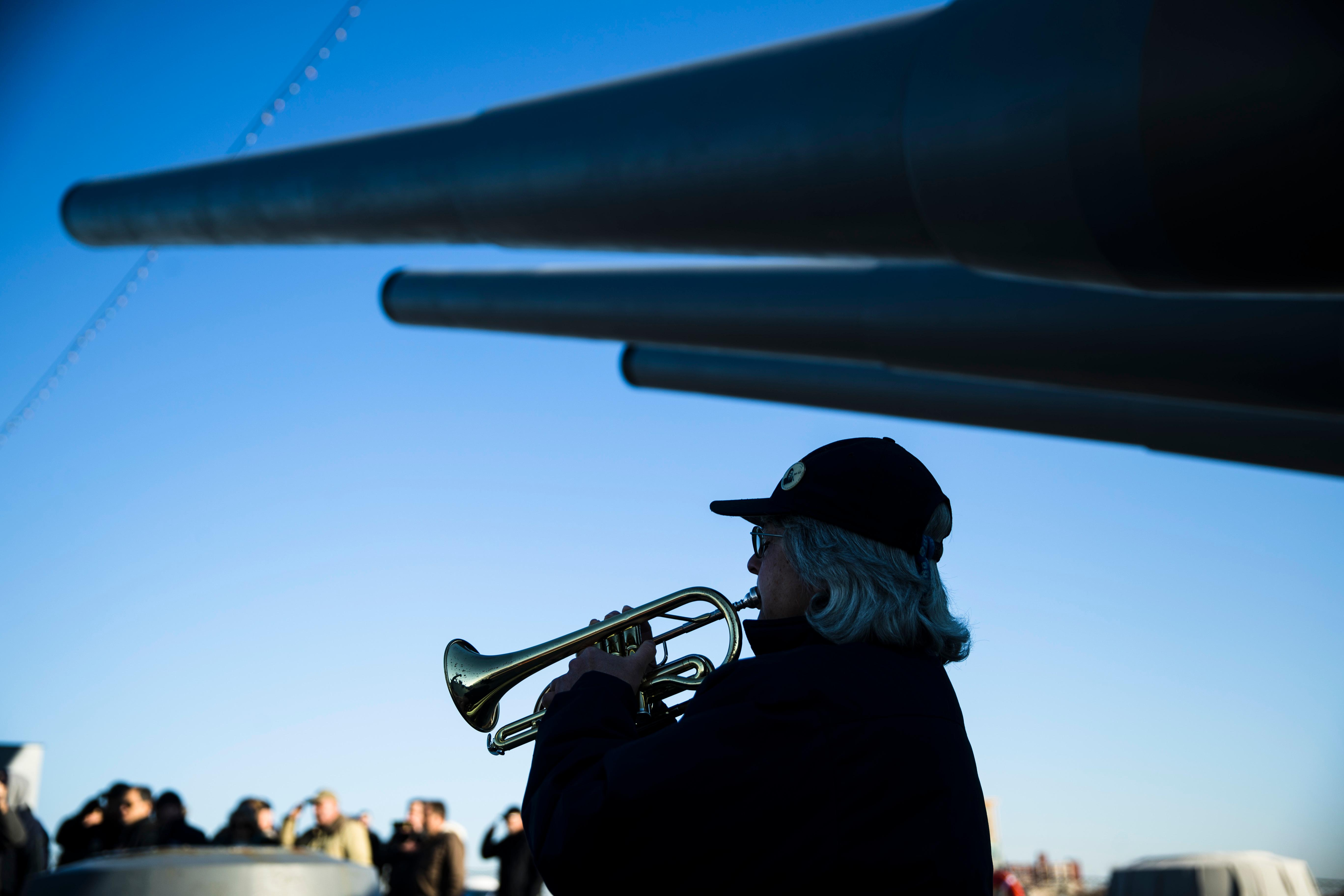 Bugler Nan LaCorte play taps during a ceremony commemorating the anniversary of the Dec. 7, 1941 Japanese attack on Pearl Harbor, on board The Battleship New Jersey Museum and Memorial in Camden, N.J., Thursday, Dec. 7, 2017. (AP Photo/Matt Rourke)