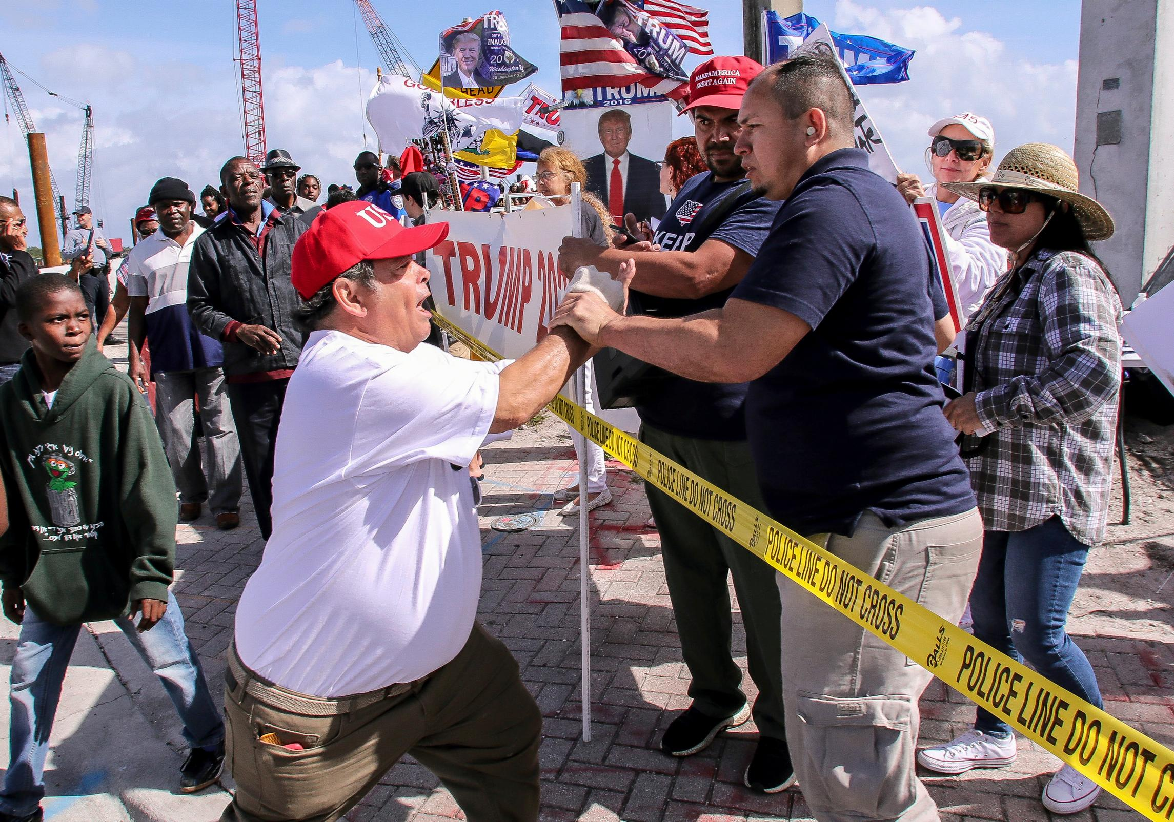 A President Donald Trump supporter, left, confronts a fellow Trump supporter, right, who was speaking on a bullhorn, to stop being disrespectful and spewing hate Monday, Jan. 15, 2018, as local Haitians march in protest of Trump in West Palm Beach, Fla. Trump is defending himself anew against accusations that he is racist, this time after recent disparaging comments about Haiti and African nations. (Damon Higgins/Palm Beach Post via AP)