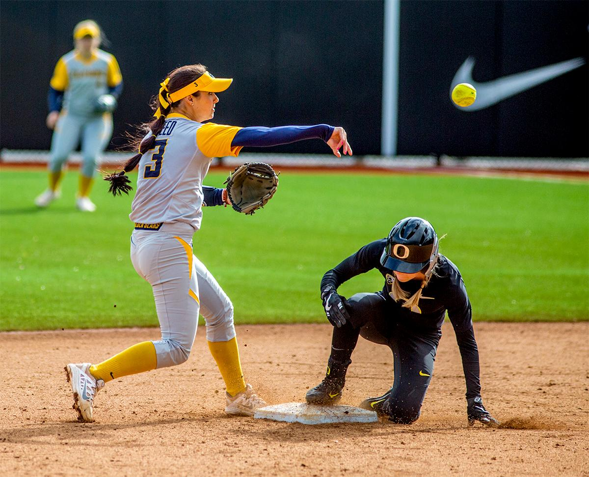 The Golden Bears' Kylie Reed (#3) makes the catch to knock a Ducks player out and throws over to first. The Oregon Ducks defeated the Cal Golden Bears 2-1 in the second game of the three game series. Photo by August Frank, Oregon News Lab